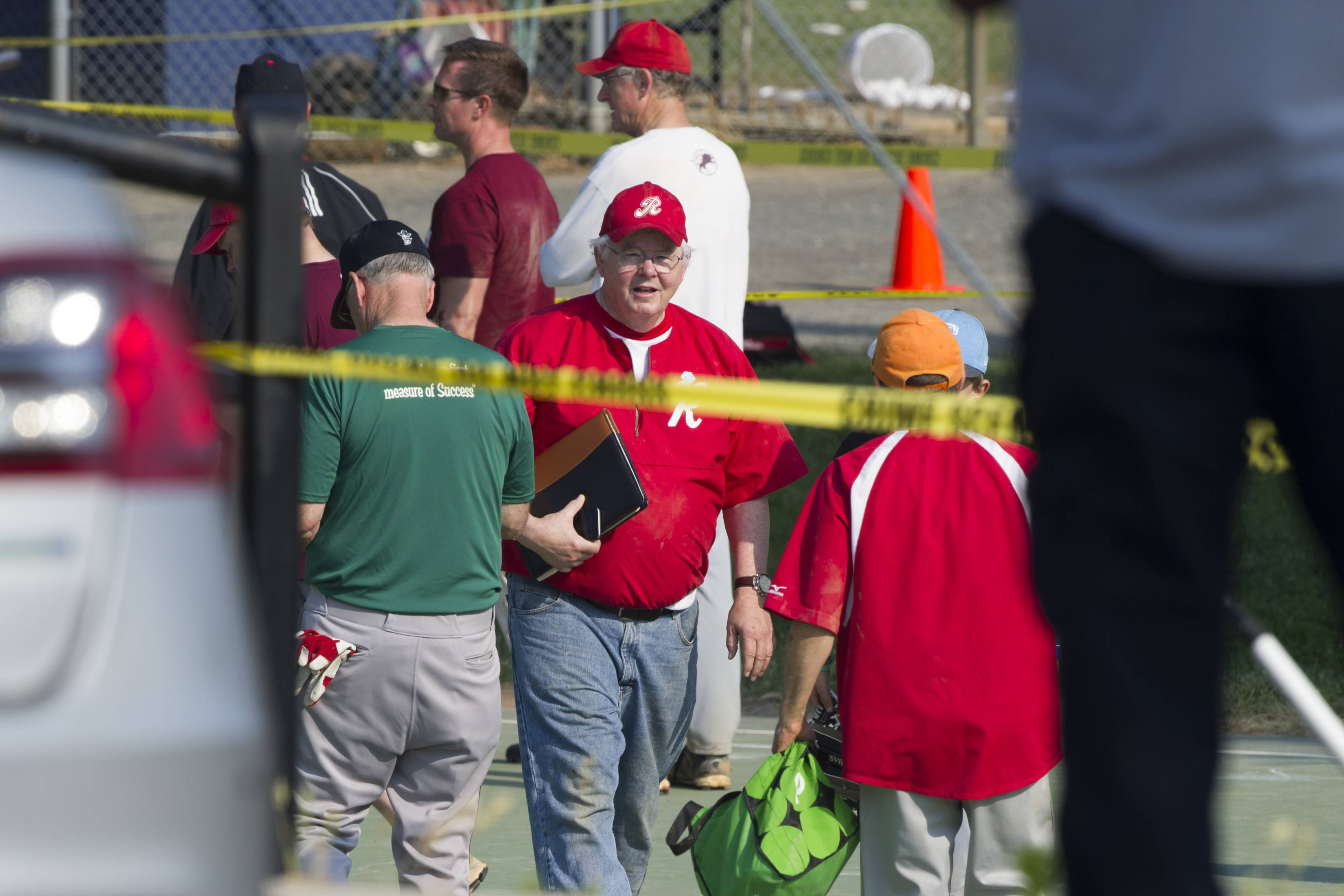 Rep. Joe Barton, R-Texas, center, and other members of the Republican Congressional softball team stand behind police tape of the scene of a multiple shooting in Alexandria, Va., Wednesday.