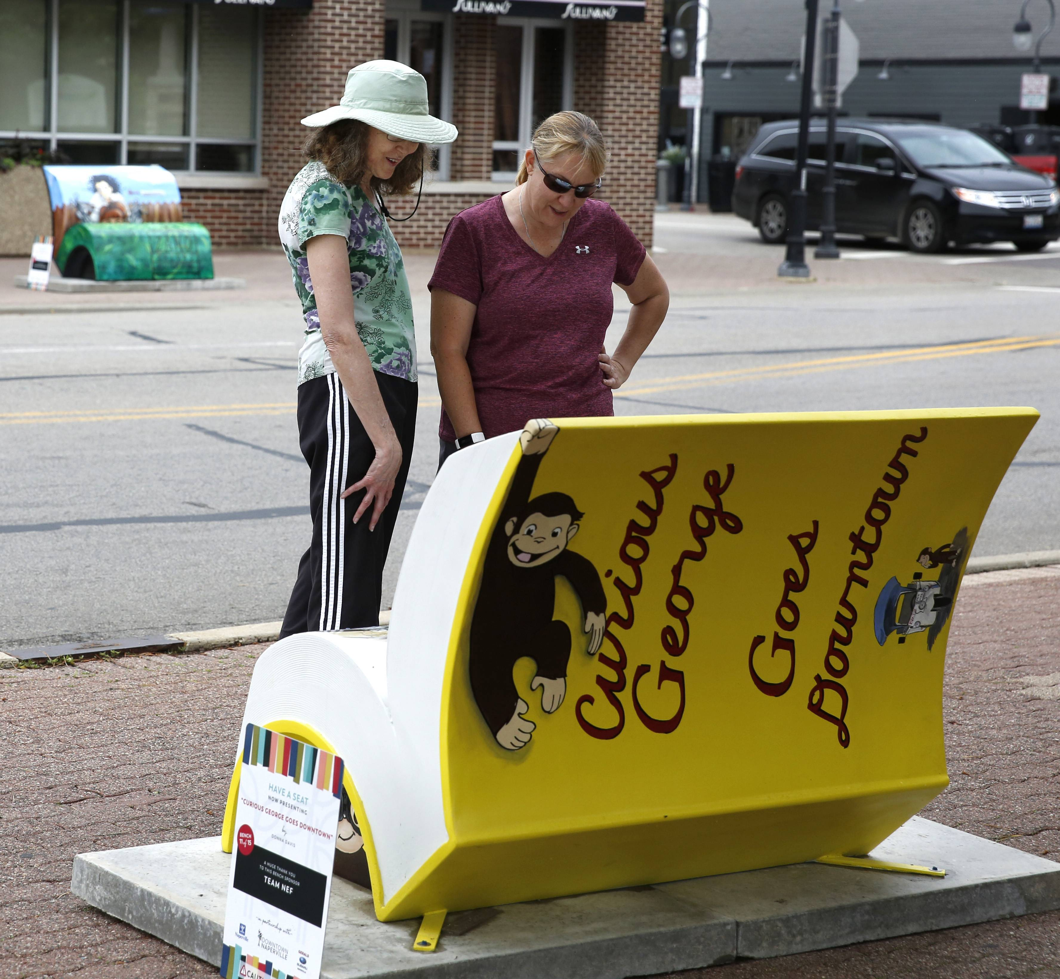 "Naperville residents Patrice Basso and Julie Lewis observe the ""Curious George Goes Downtown"" book bench by Donna Davis. The bench, at Jackson Avenue and Main Street, is one of 15 installed for the summer as part of the Downtown Naperville Alliance's annual sculpture program."