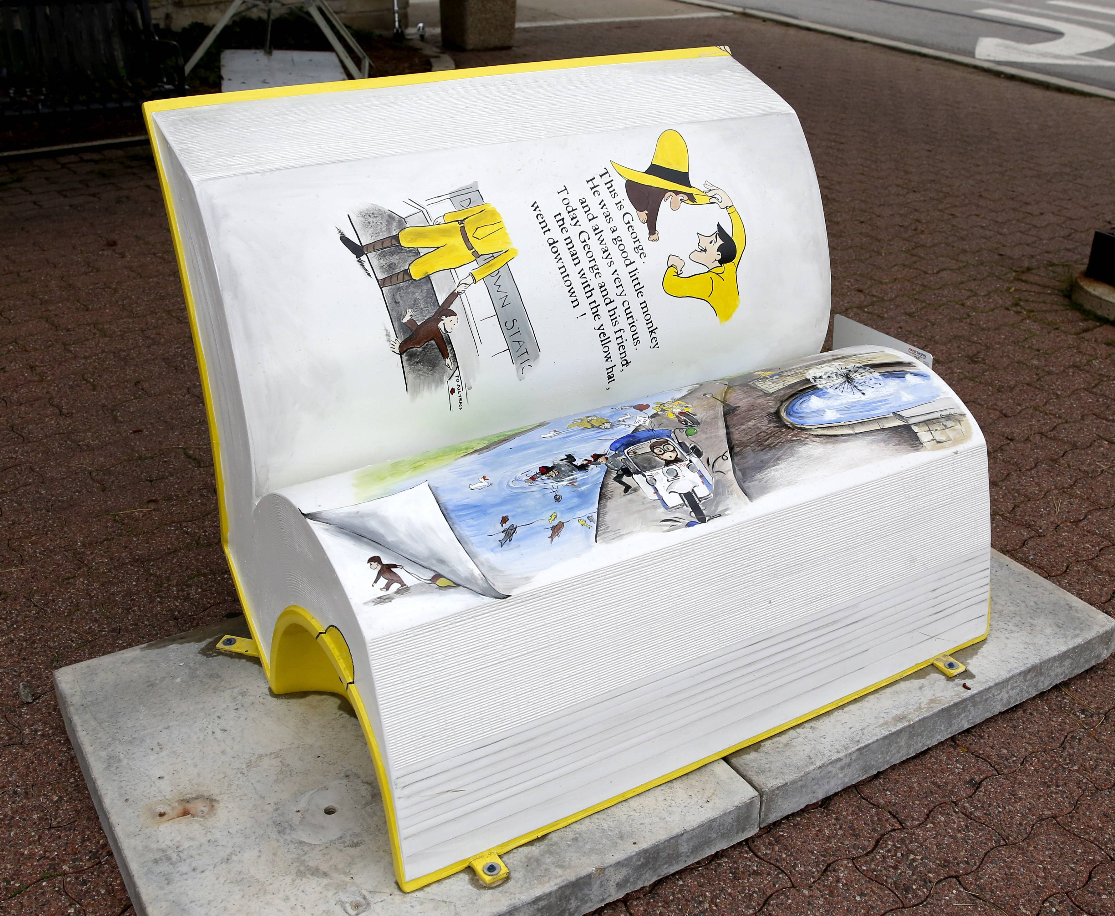 "Pages of the ""Curious George Goes Downtown"" book bench sculpture unfold Friday at Jackson Avenue and Main Street, shortly after the sculpture was installed as part of the Downtown Naperville Alliance's annual art display."