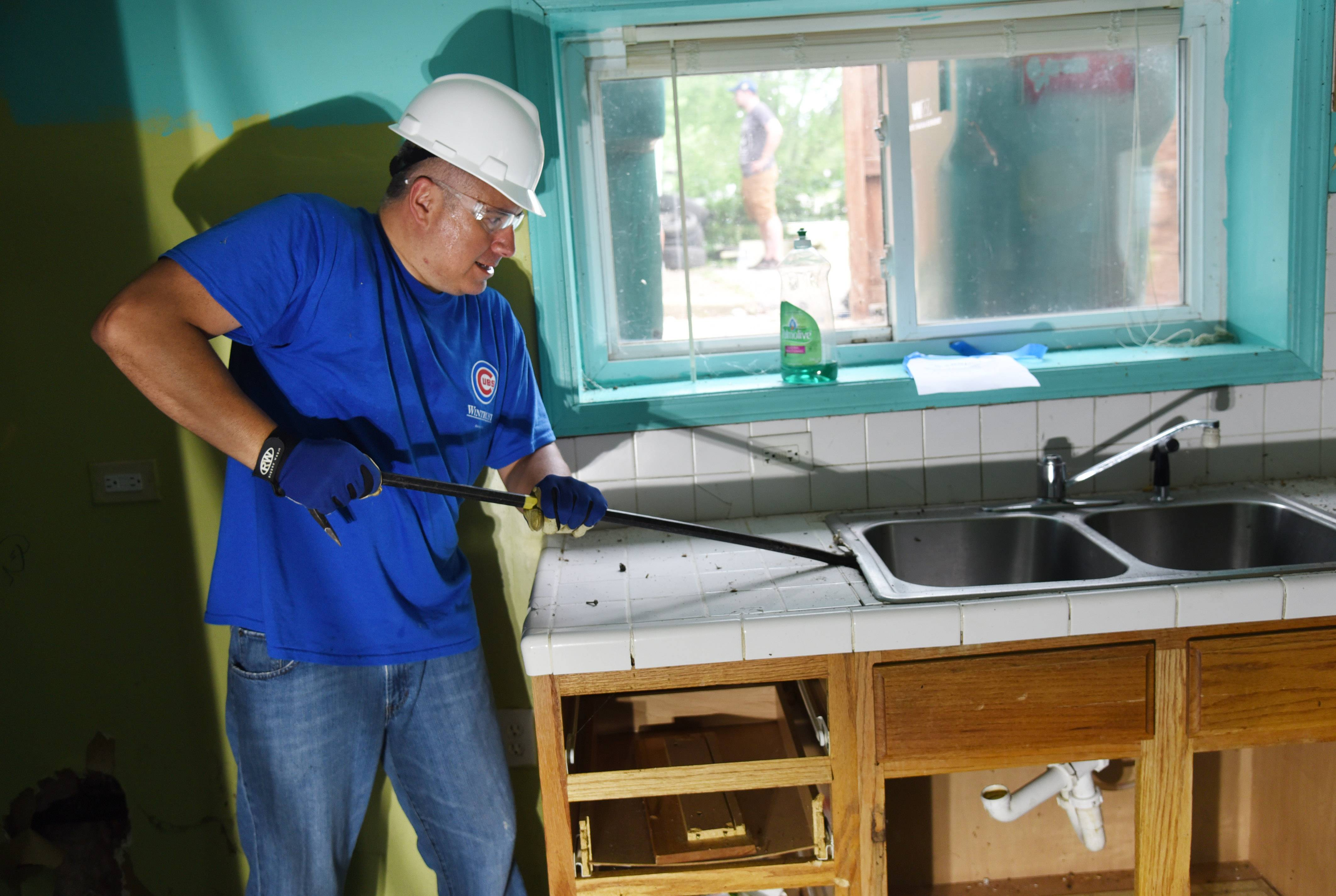 Grayslake volunteer Carlos Rosado removes a sink from the lower level of a house on Woodland Drive in Round Lake Beach Friday morning. The house was bought out of foreclosure to be rehabbed and sold at an affordable price.