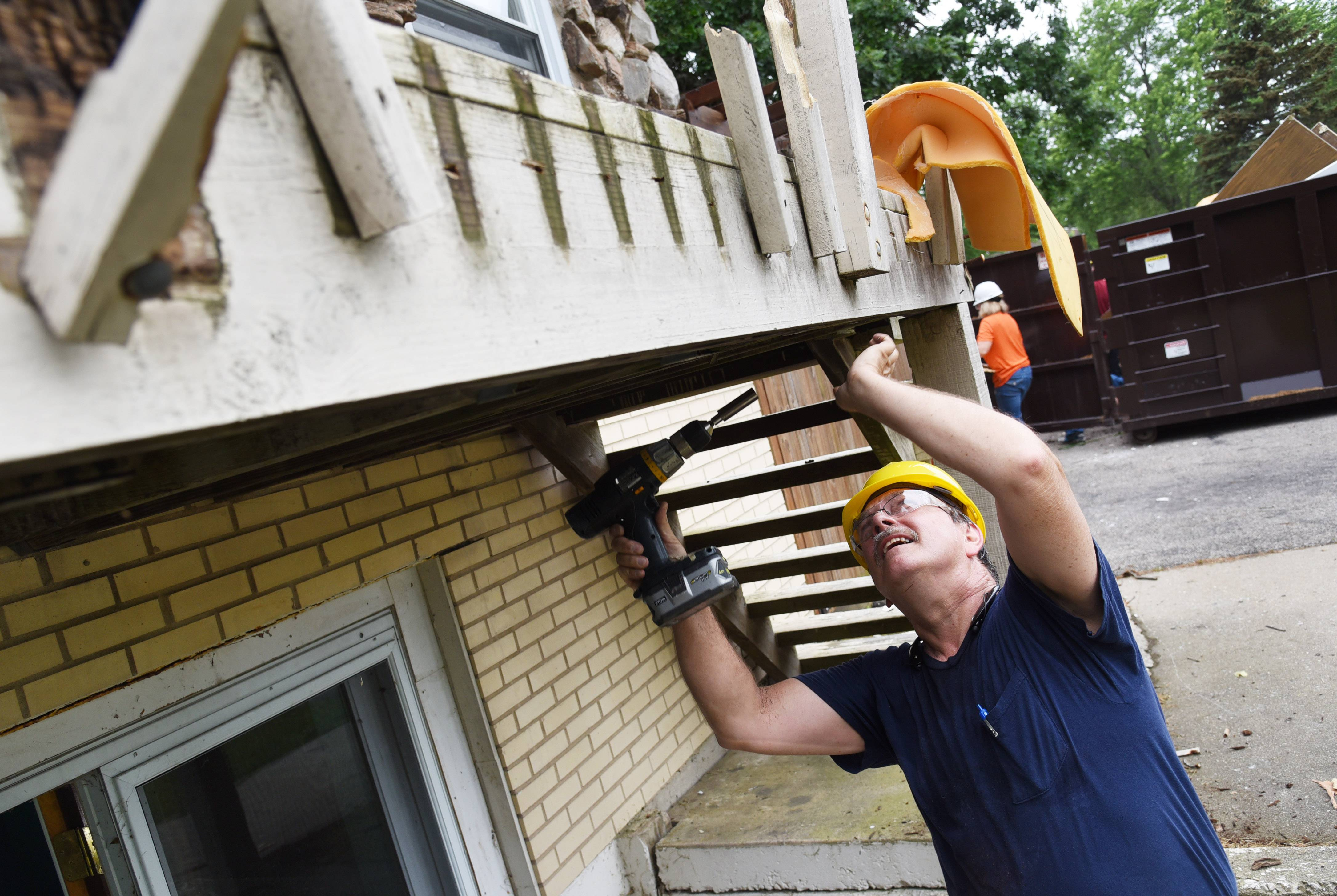 Dean DePew of The Colton Companies, Inc. in Waukegan, removes bolts from the front porch of a house on Woodland Drive in Round Lake Beach. The foreclosure was purchased by the Affordable Housing Corporation of Lake County and will be rehabbed and resold at an affordable price.