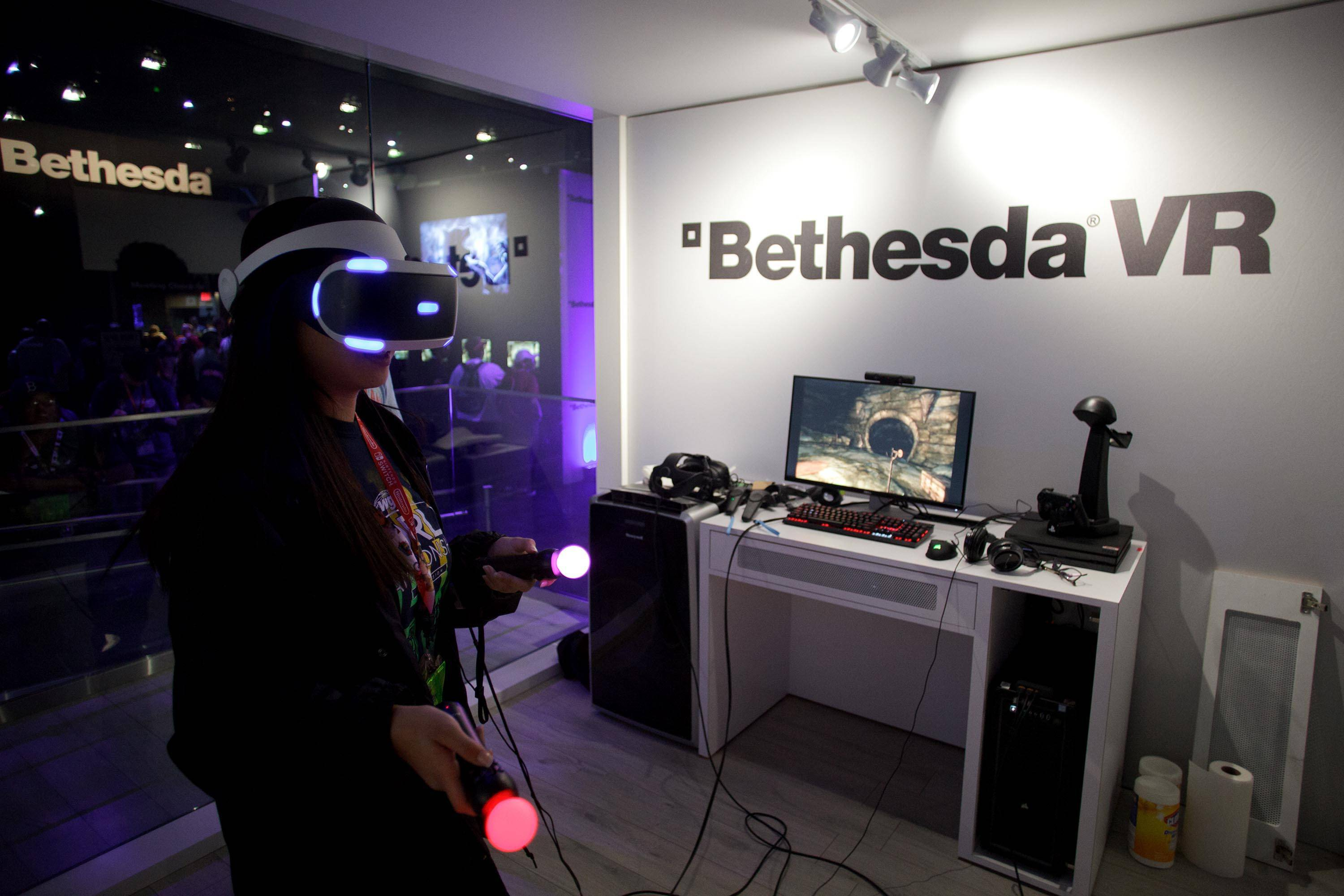 "An attendee wears a virtual reality headset while playing the Bethesda Softworks ""The Elder Scrolls V: Skyrim"" video game during the Electronic Entertainment Expo in Los Angeles on June 14, 2017."