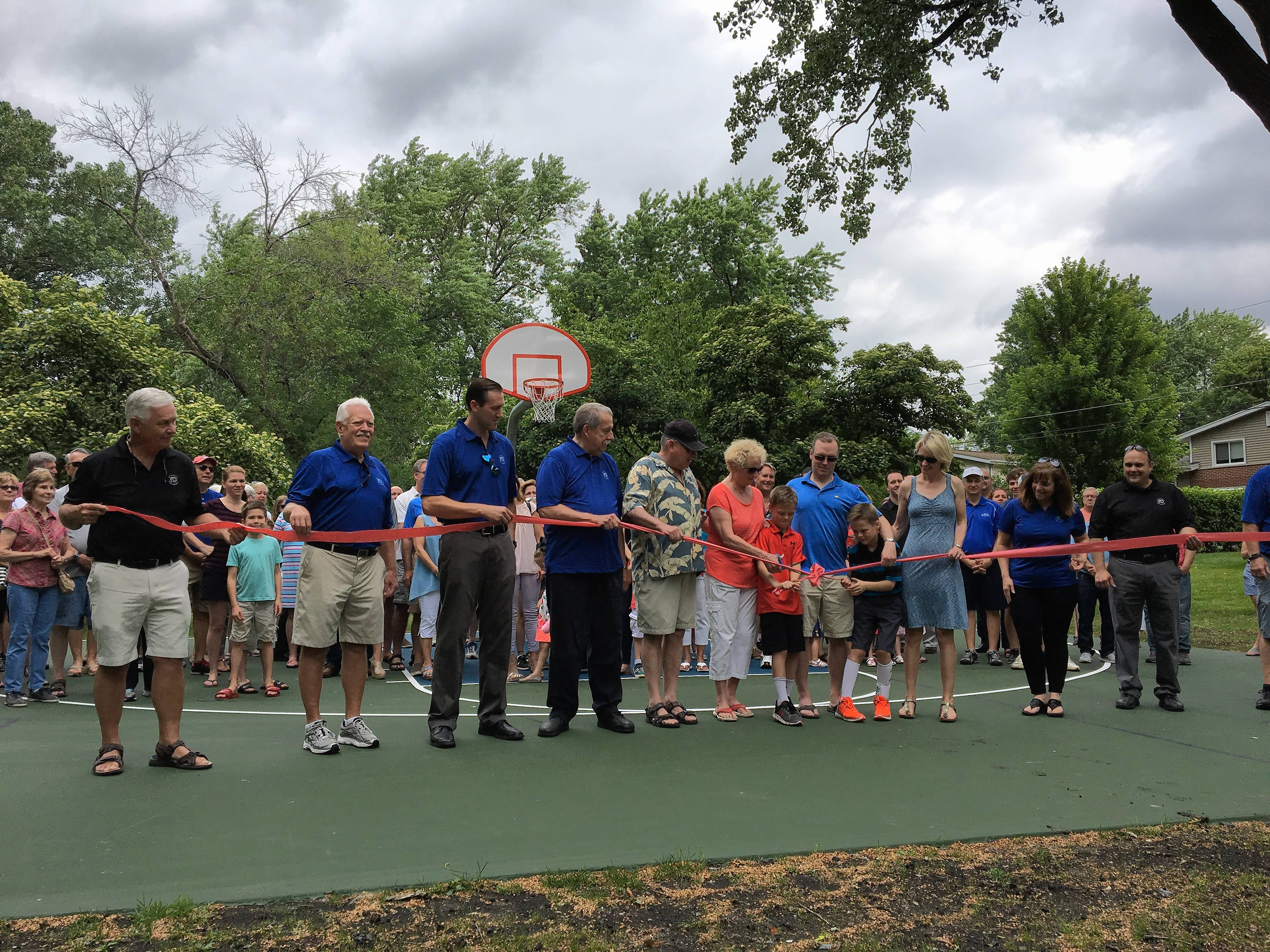 Bruce and Marta Gillilan of Mount Prospect, center, donated $15,000 toward the building of this basketball court in their neighborhood We-Go Park. It was dedicated Saturday in memory of their daughter Lindsay. Lindsay's sister Kara and her husband Colin Murphy of Wheaton, and their twin sons, Aidan and Quinn, 10, were also present.