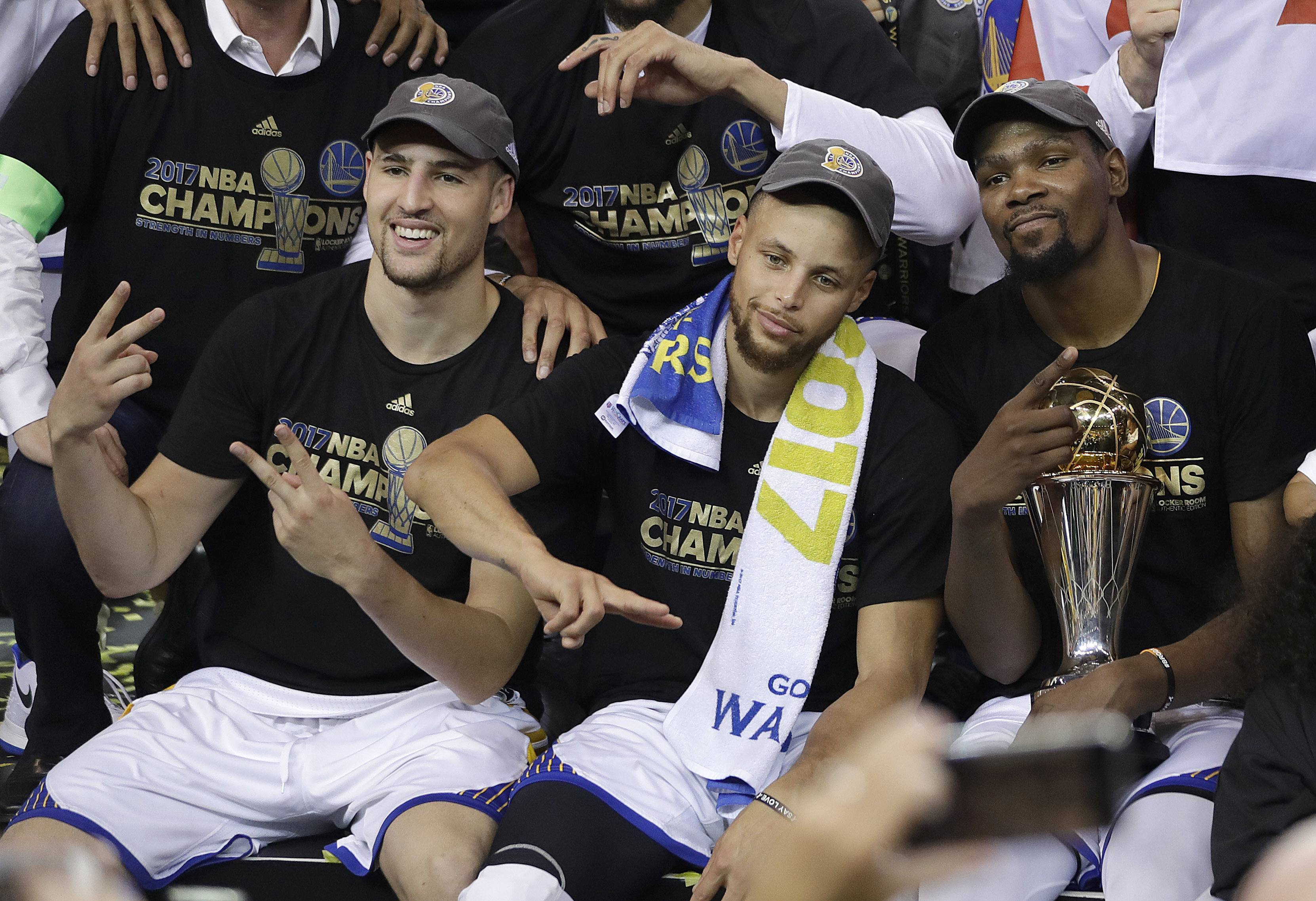 Golden State Warriors guard Klay Thompson, from left, guard Stephen Curry and forward Kevin Durant celebrate after Game 5 of basketball's NBA Finals against the Cleveland Cavaliers in Oakland, Calif., Monday, June 12, 2017. The Warriors won 129-120 to win the NBA championship.