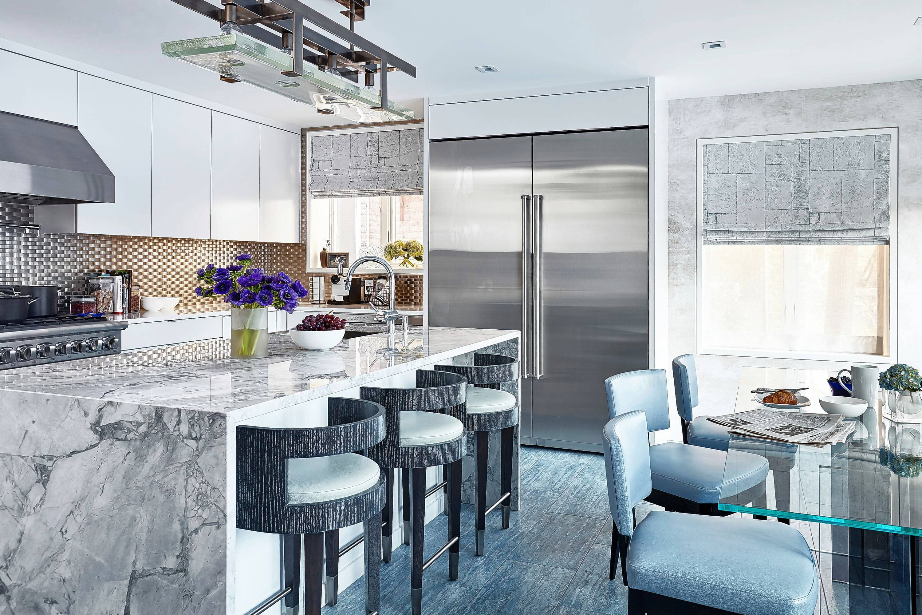 Although kitchen backsplashes are often made of porcelain or ceramic tile, interior designer Jenny Kirschner used stainless steel to give this open, airy kitchen a fresh, modern look.