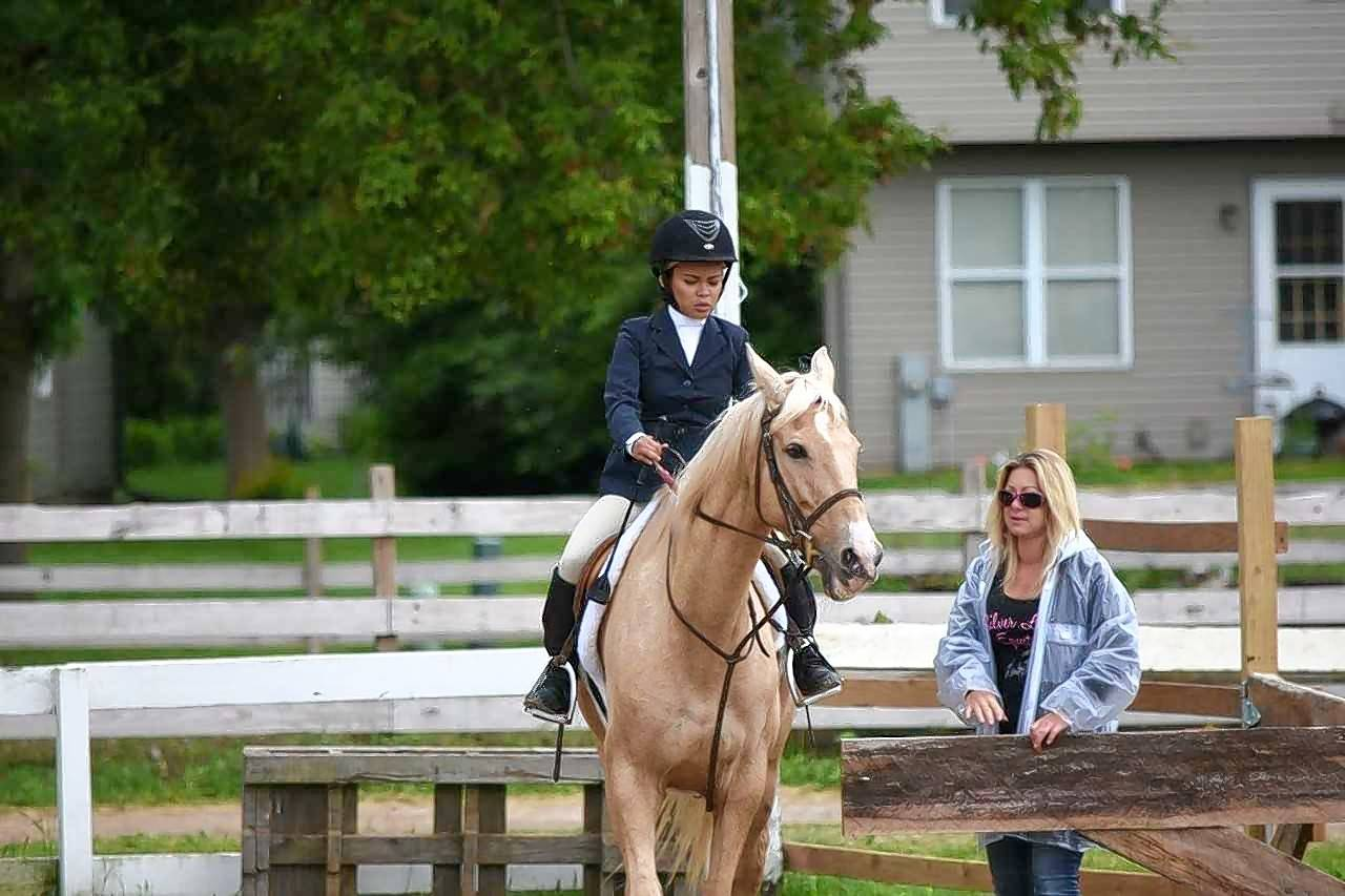 Tricia Sales, owner of Silver Lining Equestrian center in Lake in the Hills, lets rider Jehan Alvarado of Algonquin into the arena. The village evicted Sales' business last week due to compliance issues with her lease on village-owned property, according to officials.