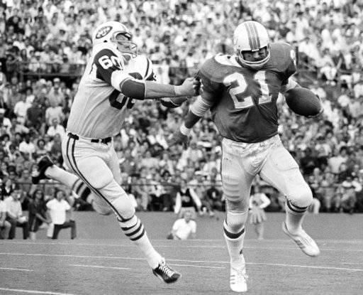 FILE - In this Dec. 13, 1970, file photo, New York Jets linebacker Larry Grantham (60) catches Miami Dolphins back Jim Kiick (21), by the sleeve to throw him for a one-yard loss on an attempted end run in an NFL football game in Miami. Grantham, a starter and defensive standout on the 1969 Super Bowl team, has died. He was 78. The Jets announced Sunday, June 18, 2017, that a funeral service for Grantham will be held Wednesday in his hometown of Crystal Springs, Miss.