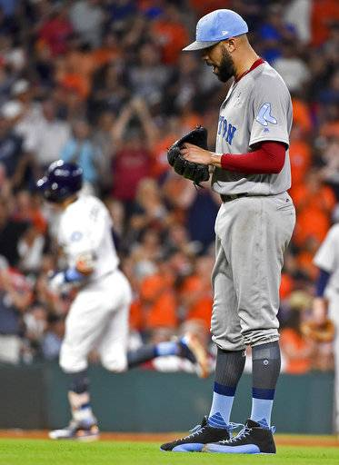 Boston Red Sox starting pitcher David Price, right, reacts as Houston Astros' Carlos Correa, left, rounds the bases after hitting a solo home run during the fifth inning of a baseball game, Sunday, June 18, 2017, in Houston.