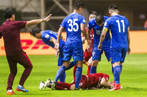 In this Sunday, June 18, 2017 photo, Guangzhou R&F players in blue jersey surround Shanghai SIPG player Oscar on the ground after being tackled during their Chinese Super League match in Guangzhou in south China's Guangdong province. Former Chelsea player Oscar sparked a bench-clearing tussle in the Chinese Super League game between Shanghai SIPG and Guangzhou R&F on Sunday after twice kicking the ball into players at close range. (Color China Photo via AP)