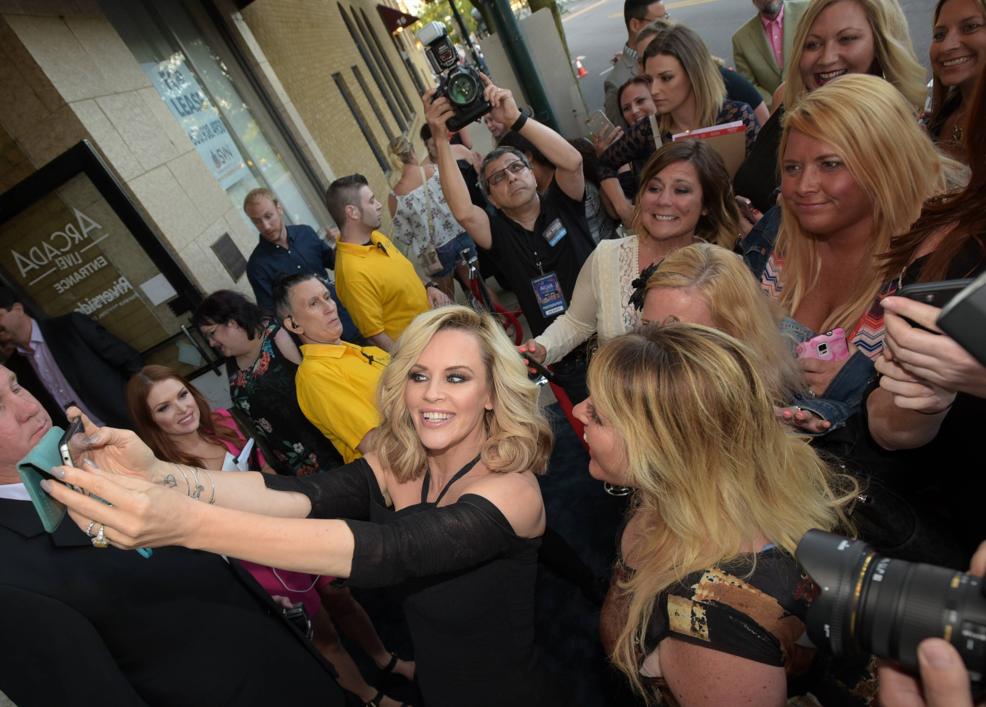 Jenny McCarthy takes a selfie with a group of fans Monday before her husband, Donnie Wahlberg, performs a benefit concert in St. Charles at the to Arcada Theatre.