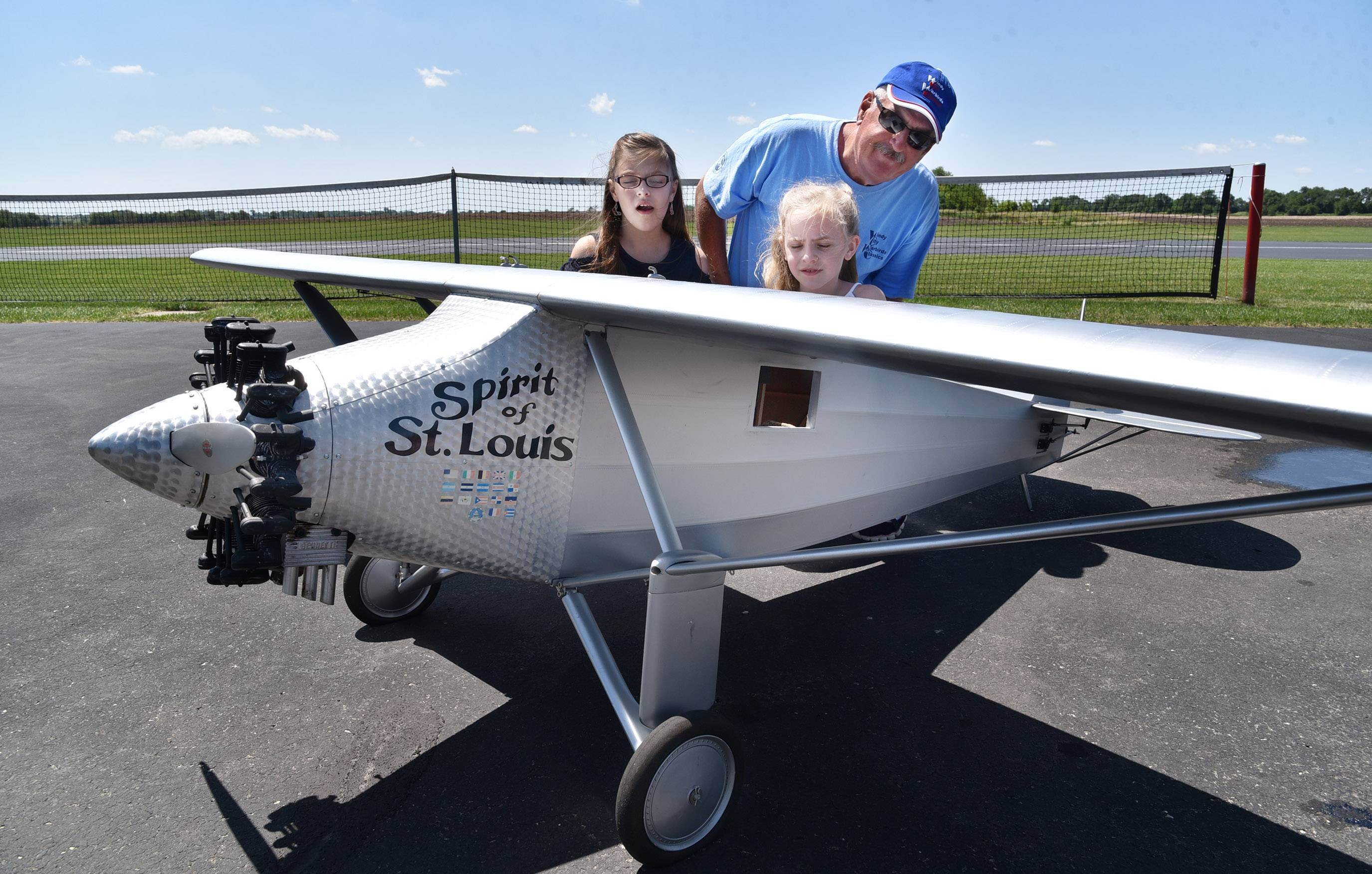 Club member Tom Flint of Geneva shows his granddaughters Madeline, 10, and Eleanor, 8, a ¼-scale model remote-controlled duplicate of the Spirit of St. Louis airplane at the Fox Valley Aero Club airstrip in St. Charles. The plane will be one of dozens, perhaps hundreds, on hand at the club's annual Warbirds and Classics show on June 22-24.