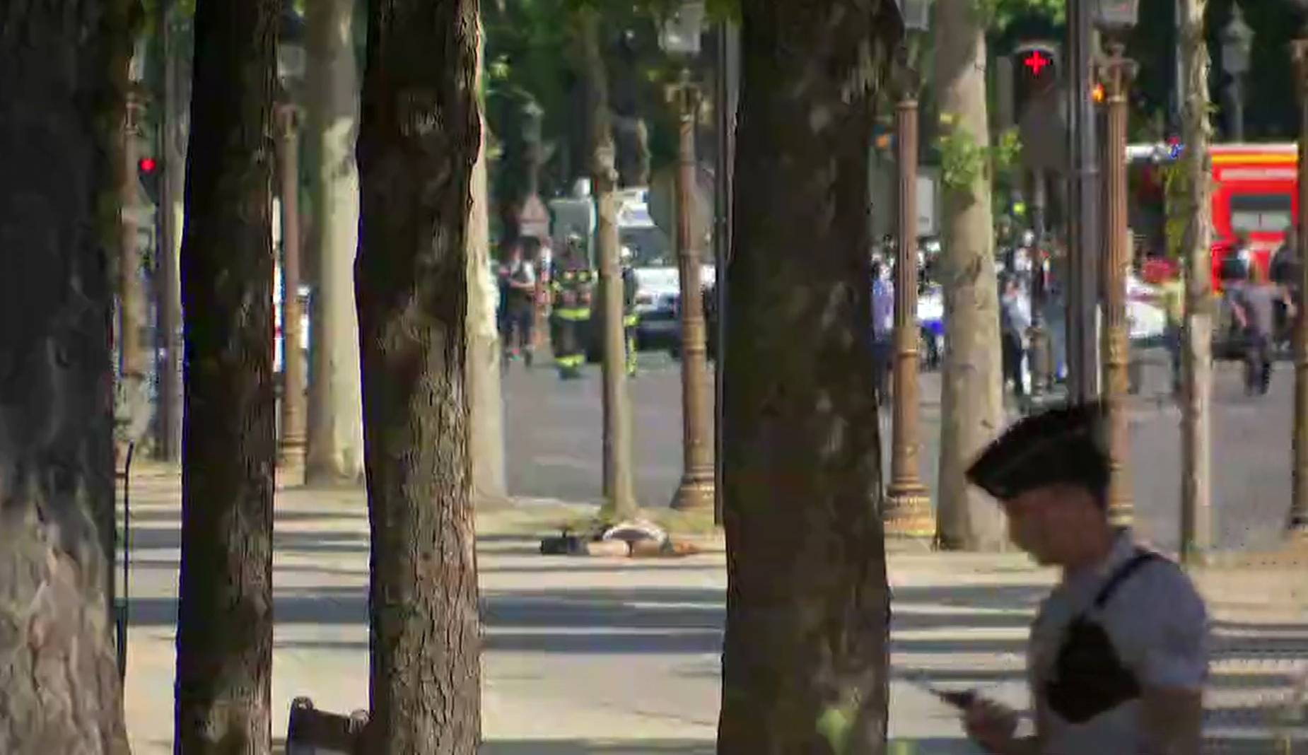 A person is seen on the ground as a police officer is seen in the foreground on the Champs Elysees avenue in Paris, France, Monday. France's anti-terrorism prosecutor has opened an investigation into the ramming of a police vehicle on Paris' Champs-Élysées avenue. Authorities say a driver has rammed his car into a police vehicle in the Champs-Élysées shopping district. They say he has been arrested after being injured in a subsequent apparent clash with police. The condition of the person on the ground is not known.