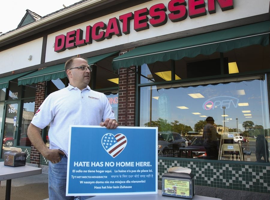 "Howard Bender, owner of Schmaltz Jewish Delicatessen in Naperville, is putting up ""Hate Has No Home Here"" posters in his window after someone vandalized his sidewalk with a political message."