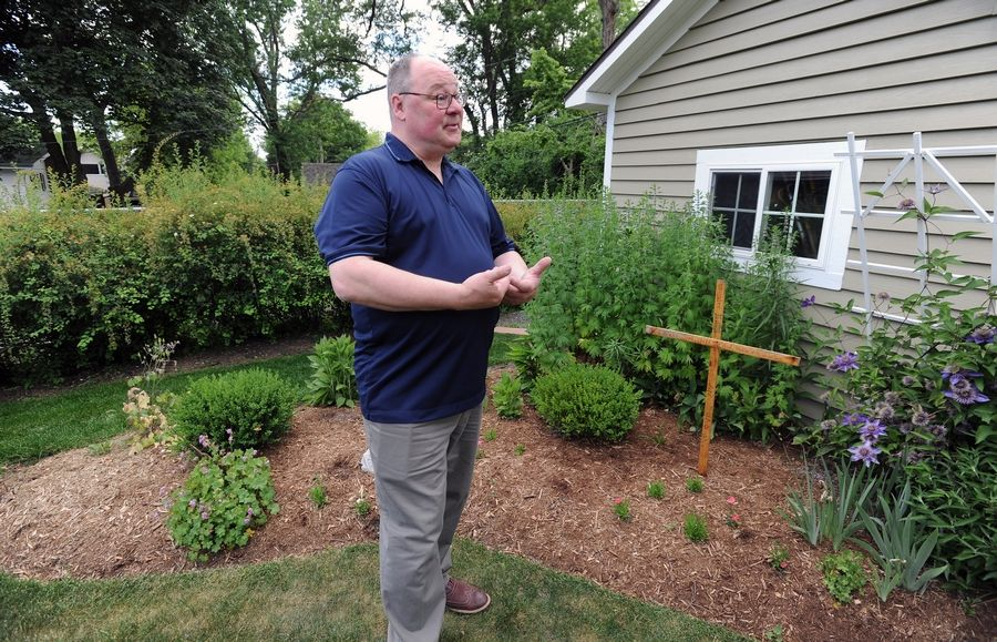 Eric Jakubowski of Mount Prospect takes comfort in his wife Joni Beaudry's garden, where friends planted flowers after she was killed by a driver at a controversial crossing a year ago.