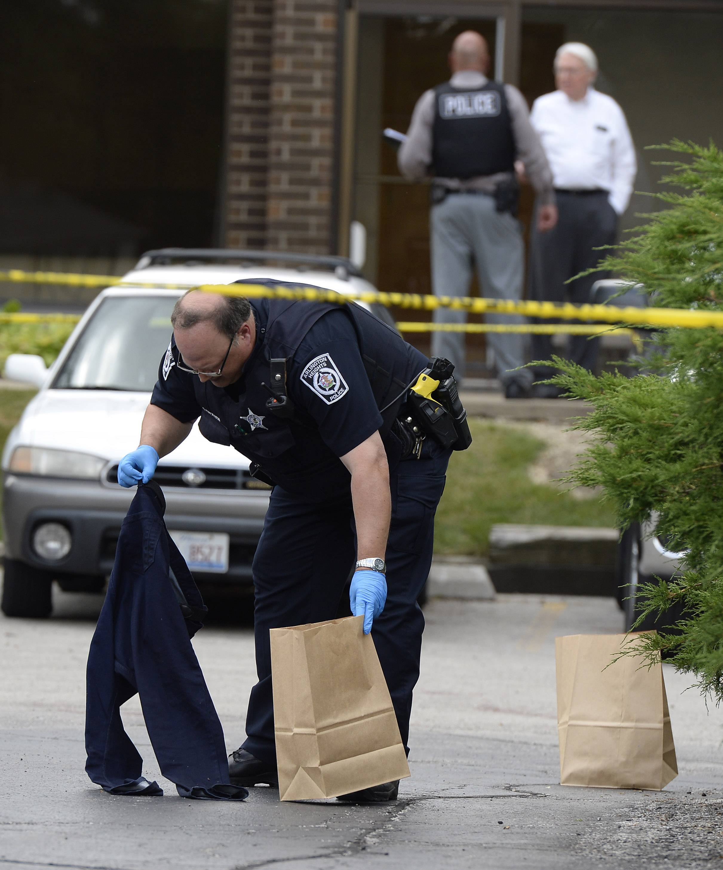 Arlington Heights police gather evidence, including bloody clothes and a chain saw, after a domestic dispute that turned violent in a parking lot Monday.