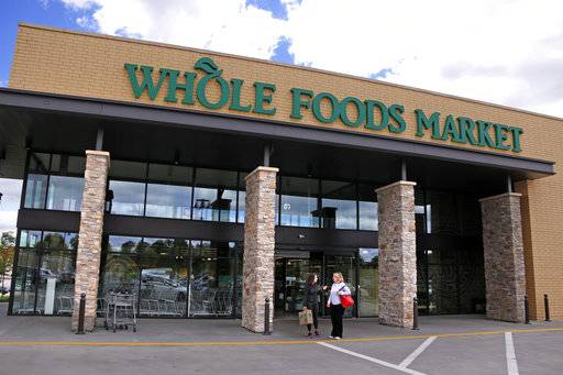 In this May 3, 2017, photo, people stand outside a Whole Foods Market in Upper Saint Clair, Pa. Amazon's planned $13.7 billion acquisition of Whole Foods signals a massive bet that people will opt more for the convenience of online orders and delivery or in-store pickup, putting even more pressure on the already highly competitive industry.
