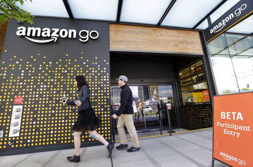 FILE - In this Thursday, April 27, 2017, file photo, people walk past an Amazon Go store, currently open only to Amazon employees, in Seattle. Amazon Go shops are convenience stores that don't use cashiers or checkout lines, but use a tracking system that of sensors, algorithms, and cameras to determine what a customer has bought. Amazon says the company has no plans to use such sensors to automate the cashier jobs at Whole Foods, which Amazon is acquiring. Still, it's the kind of technology that could help cut costs down the road, and that others may look to as well.