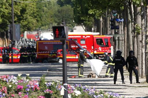 Rescue workers cover a body lying on the Champs Elysées in Paris, Monday, June 19, 2017. A driver rammed his car, partially seen at left behiong the police van, into a police vehicle in the Champs-Elysees shopping district Monday, prompting a fiery explosion, and was likely killed in the incident, authorities said. France's anti-terrorism prosecutor opened an investigation.