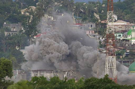 FILE - In this Friday, June 9, 2017 file photo, debris and smoke rises after a Philippine Air Force fighter jets bombed suspected locations of Muslim militants, in Marawi city, southern Philippines. Southeast Asia's jihadis who fought for the Islamic State in Iraq and Syria now have a different battle closer to home in southern Philippines. It's a scenario raising significant alarm in Washington. The recent assault by IS-aligned fighters on the Philippine city of Marawi has left almost 300 people dead, exposing the shortcomings of local security forces and the extremist group's spreading reach.