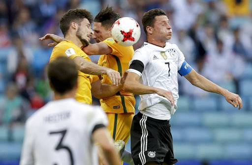 Germany's Julian Draxler, right, fight an aerial duel wit two Australian players during the Confederations Cup, Group B soccer match between Australia and Germany, at the Fisht Stadium in Sochi, Russia, Monday, June 19, 2017.