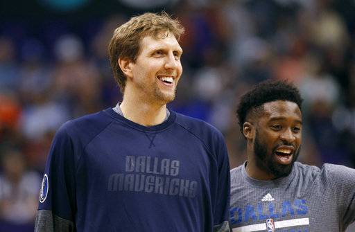 FILE - In this April 9, 2017, file photo, Dallas Mavericks forward Dirk Nowitzki, left, and teammate Wesley Matthews laugh during pre-game warm up before an NBA basketball game against the Phoenix Suns, in Phoenix. Nowitzki, the career scoring leader among international players, will be one of the captains for the NBA's Africa Game on Aug. 5.