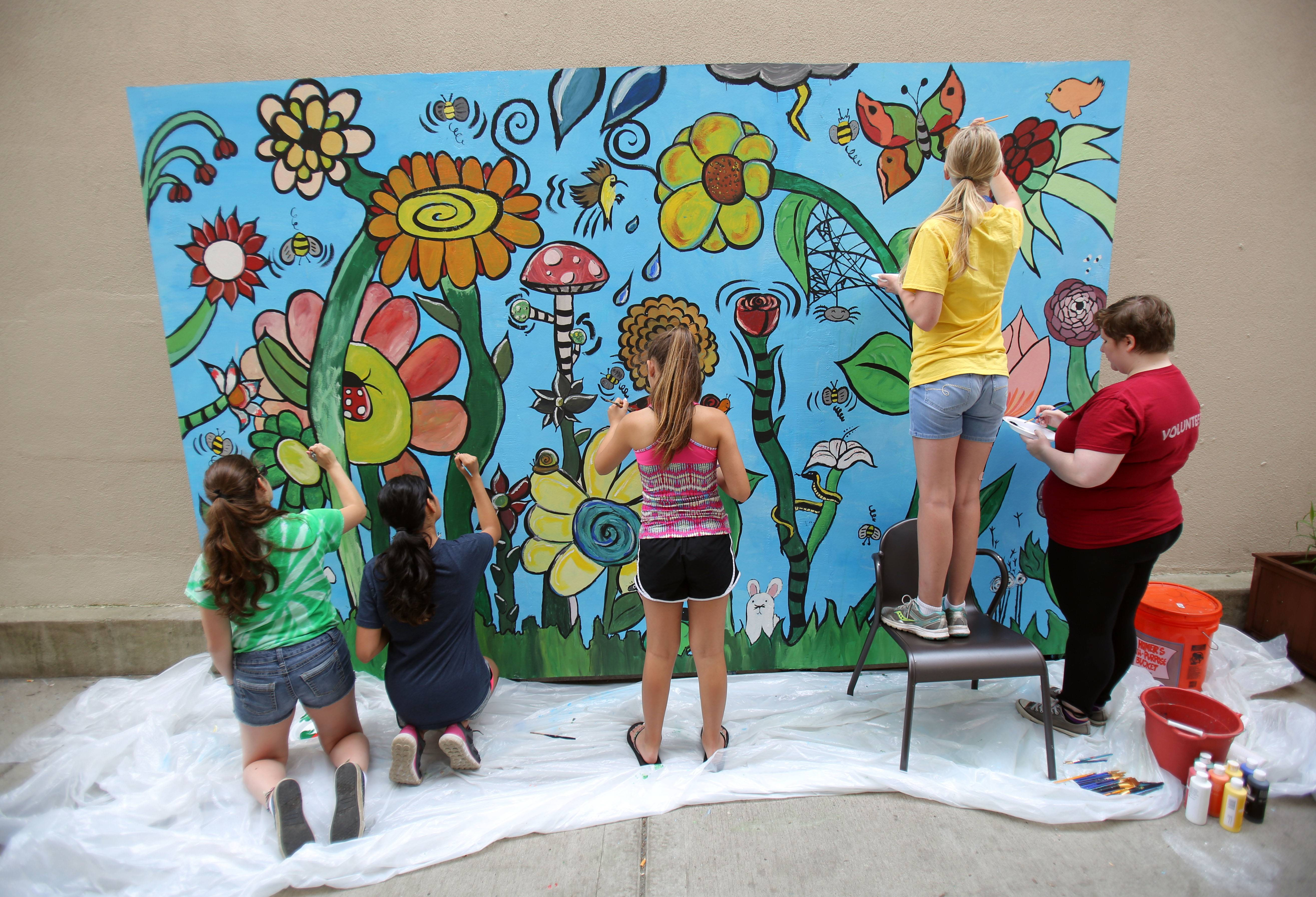 Kids from the David Adler Music and Arts Center summer camp paint a mural Thursday in Artists Alley — a walkway between Shakou and Milwalky Taco restaurants in downtown Libertyville.