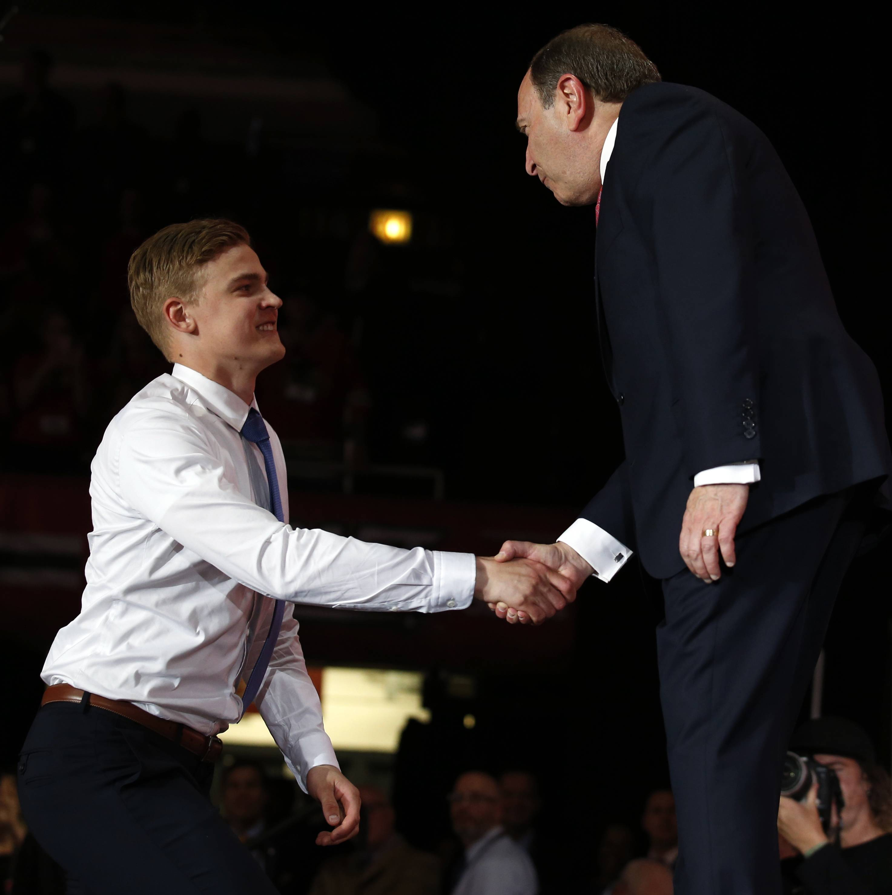 Henri Jokiharju, left, greets NHL Commissioner Gary Bettman after being selected by the Chicago Blackhawks in the first round of the NHL hockey draft, Friday, June 23, 2017, in Chicago. (AP Photo/Nam Y. Huh)