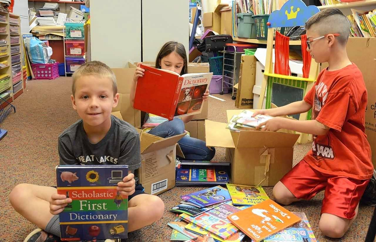 Fremont first-graders Alton Swanson, Elly Fairbrother and Ray Zuniga pack books to be donated to Kenneth Murphy Elementary School in Beach Park.