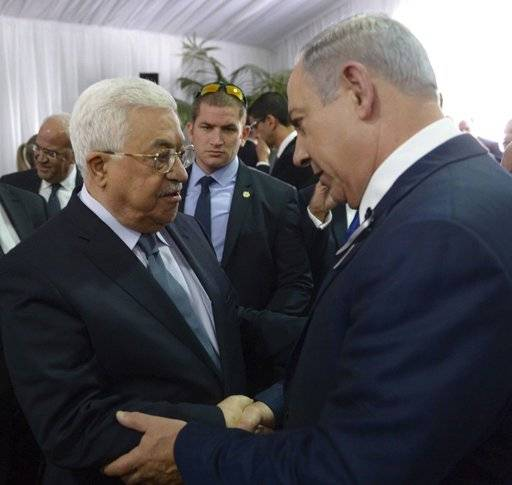 "FILE - This Sept. 30, 2016 file image released by the Israeli Government Press Office shows Palestinian President Mahmoud Abbas, left, shaking hands with Israeli Prime Minister Benjamin Netanyahu, right, at the funeral for former President Shimon Peres in Jerusalem. Donald Trump may be uniquely suited to push for a creative Middle East peace: both the Israelis and key Arab players, each for their own reasons, are looking like wary admirers who seek to please. But the reasons why Israelis and Palestinians have failed to reach a final peace agreement remain stubbornly in place, and so the search is on for an out-of-the-box ""deal.� The focus could eventually fall on a partial peace deal that breaks the diplomatic logjam by avoiding excessive ambition. (Amos Ben Gershom, Israeli Government Press Office via AP, File)"