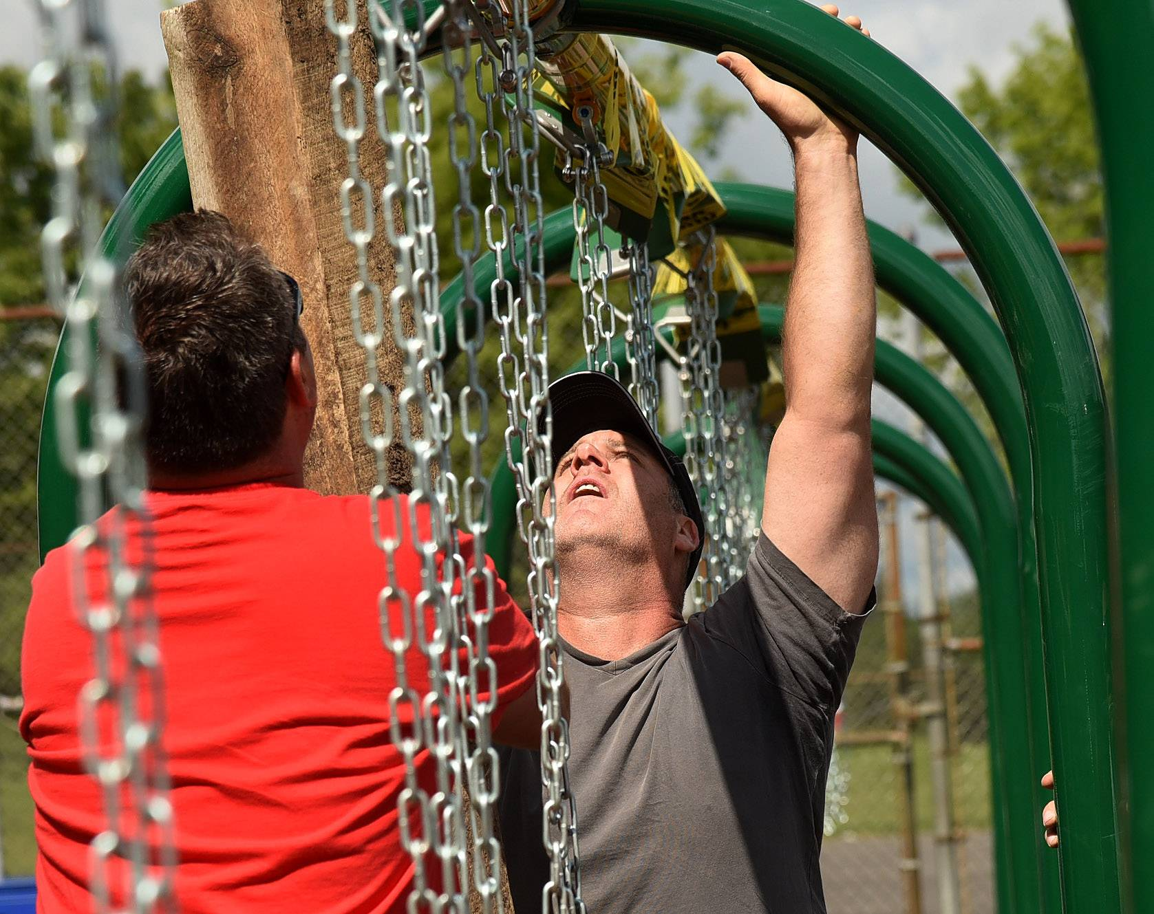 Brian McMahon and Drew Rieder work on leveling a swing set during a volunteer project to build a new playground at Butterfield School in Libertyville Saturday.
