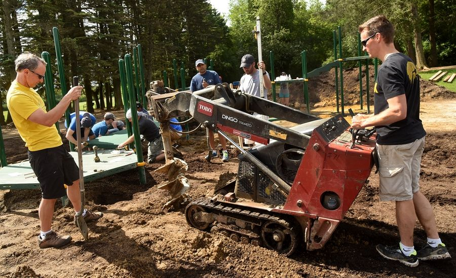 Dads Jerry Thompson, left, and Corey Weaver guide a post hole digger in place during construction of a new playground at Butterfield School in Libertyville Saturday.