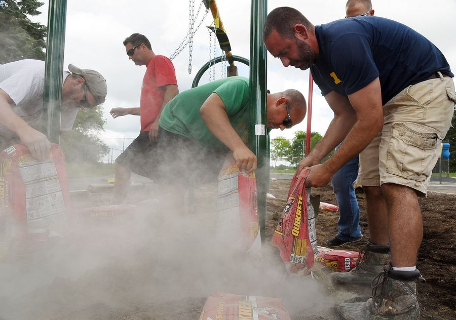 Michael Mazza, center, pours cement into a hole while assembling a swing set with other dads at Butterfield School in Libertyville Saturday.