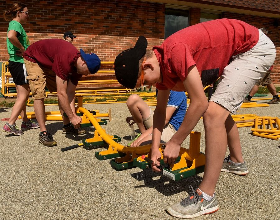 Riley Klebe, far right, helps assemble a piece of playground apparatus during the project that was months in the making.