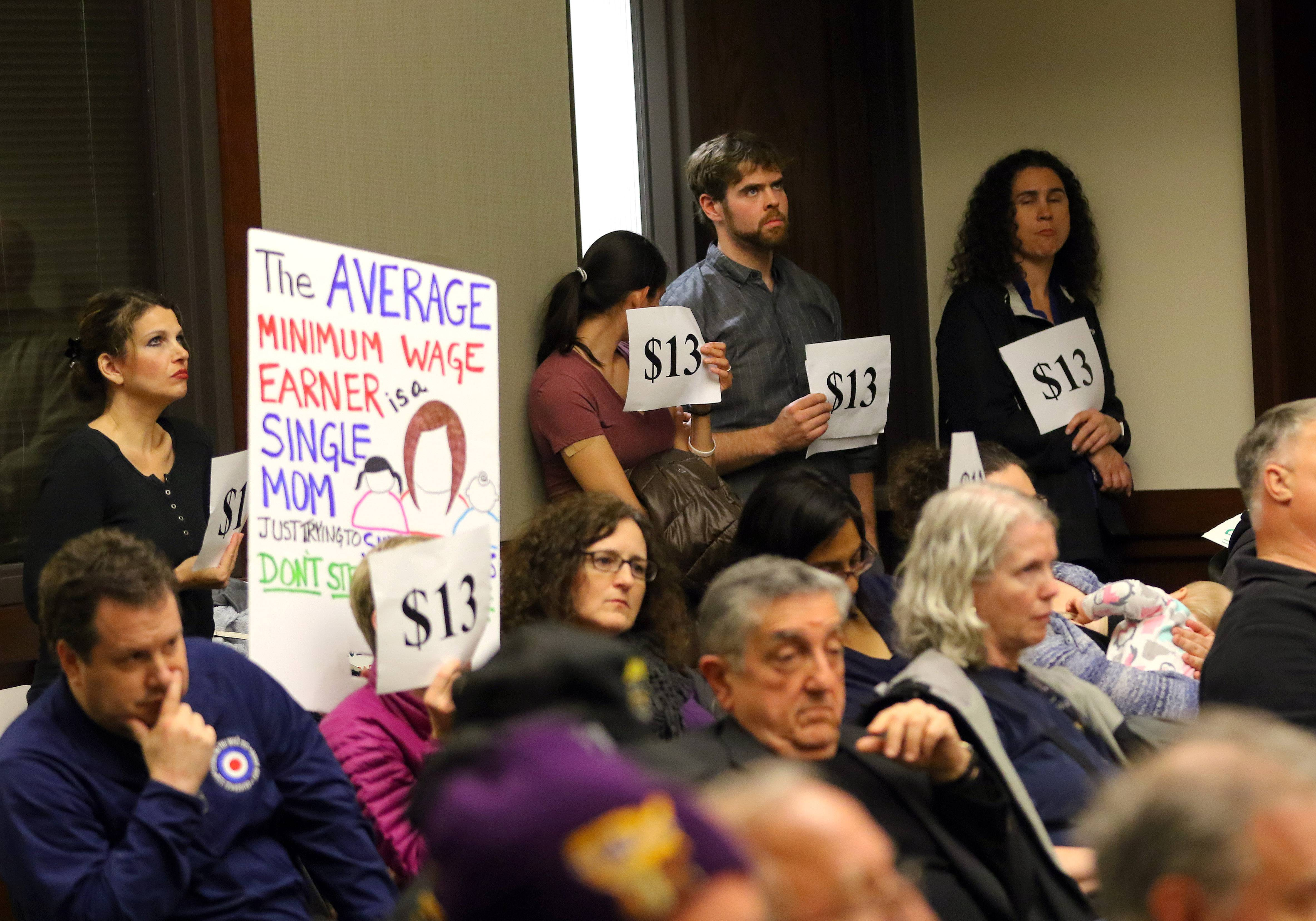 Supporters of Cook County's minimum wage and sick leave ordinances hold signs during an Arlington Heights village board meeting earlier this year. Despite the protest, Arlington Heights trustees voted to opt out of the ordinances.