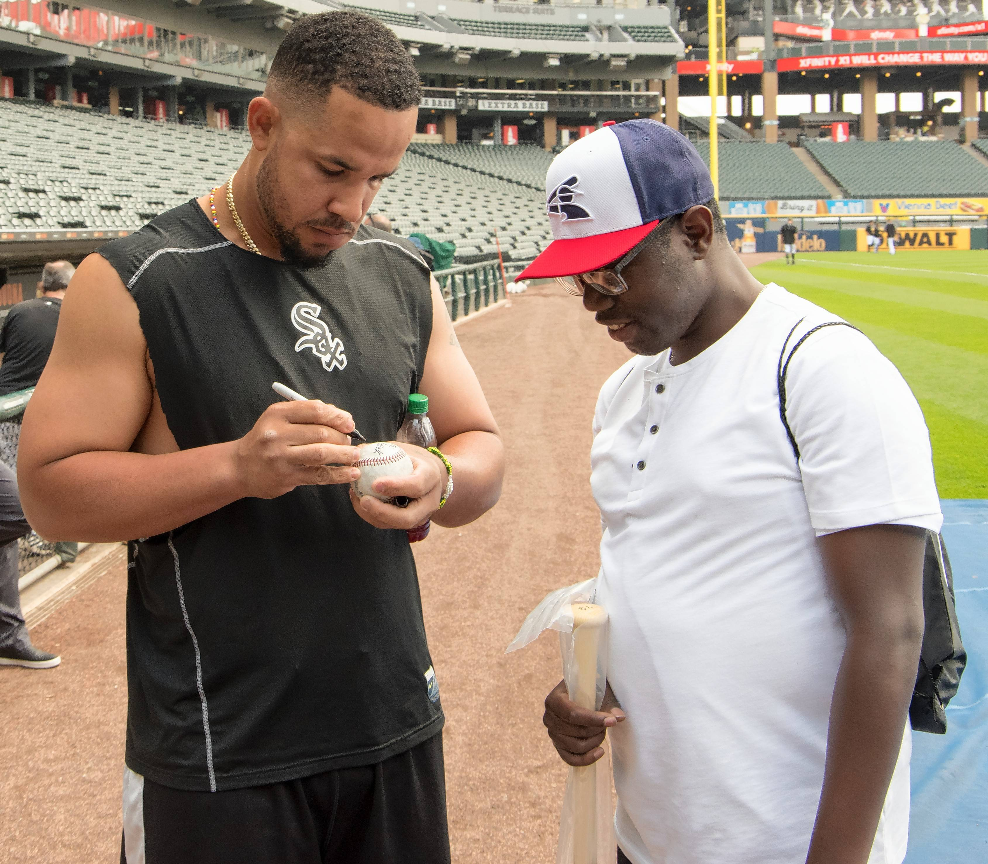 White Sox first baseman Jose Abreu, left, signs a ball, bat and gloves for Patrick Brock of Schaumburg. Brock, who has special needs and was adopted by a Schaumburg family as a foster child, grew up as a die-hard White Sox fan.