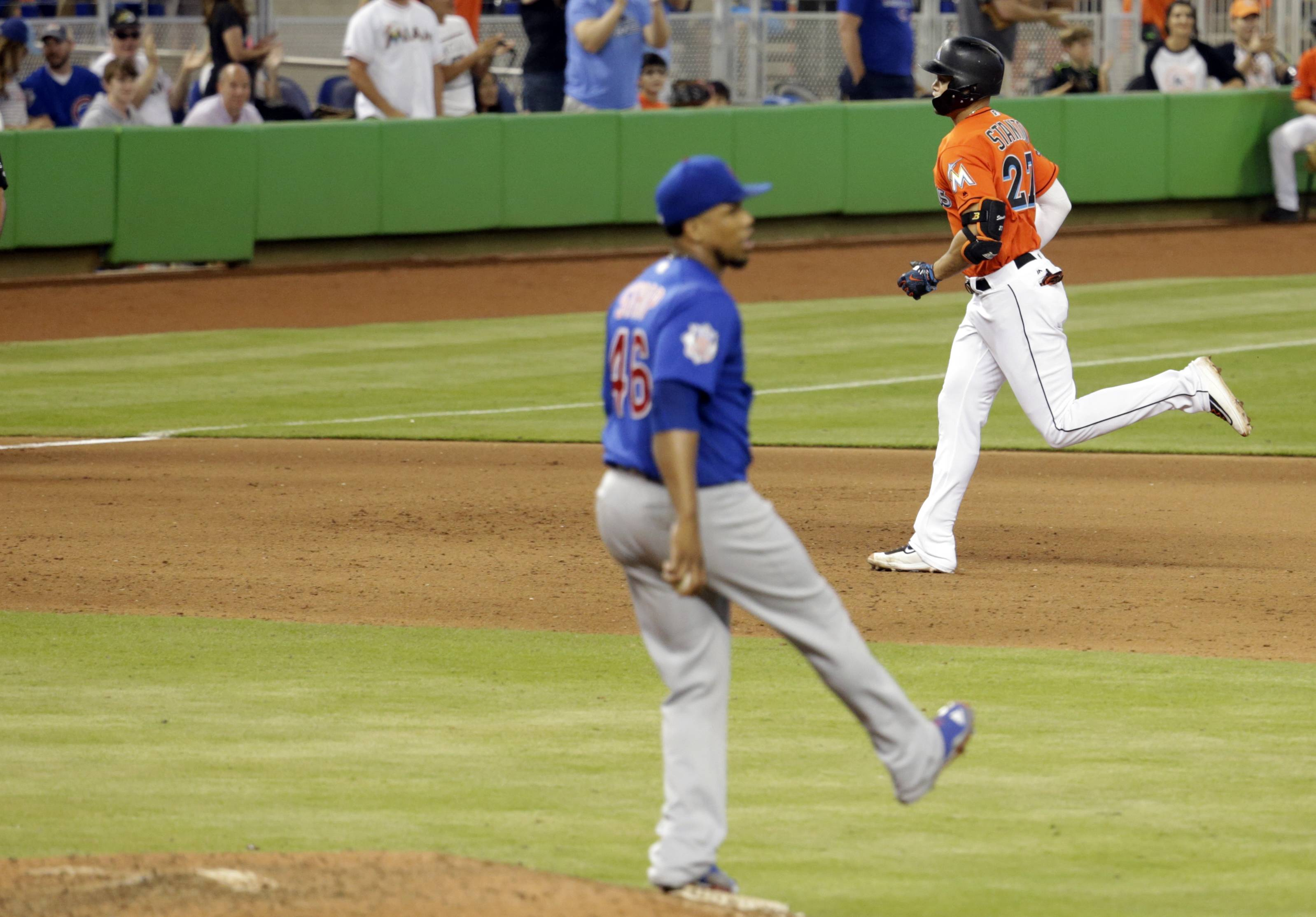 Miami Marlins' Giancarlo Stanton, right, rounds the bases after hitting a solo home run off Chicago Cubs relief pitcher Pedro Strop, left, during the seventh inning of a baseball game, Sunday, June 25, 2017, in Miami. (AP Photo/Lynne Sladky)