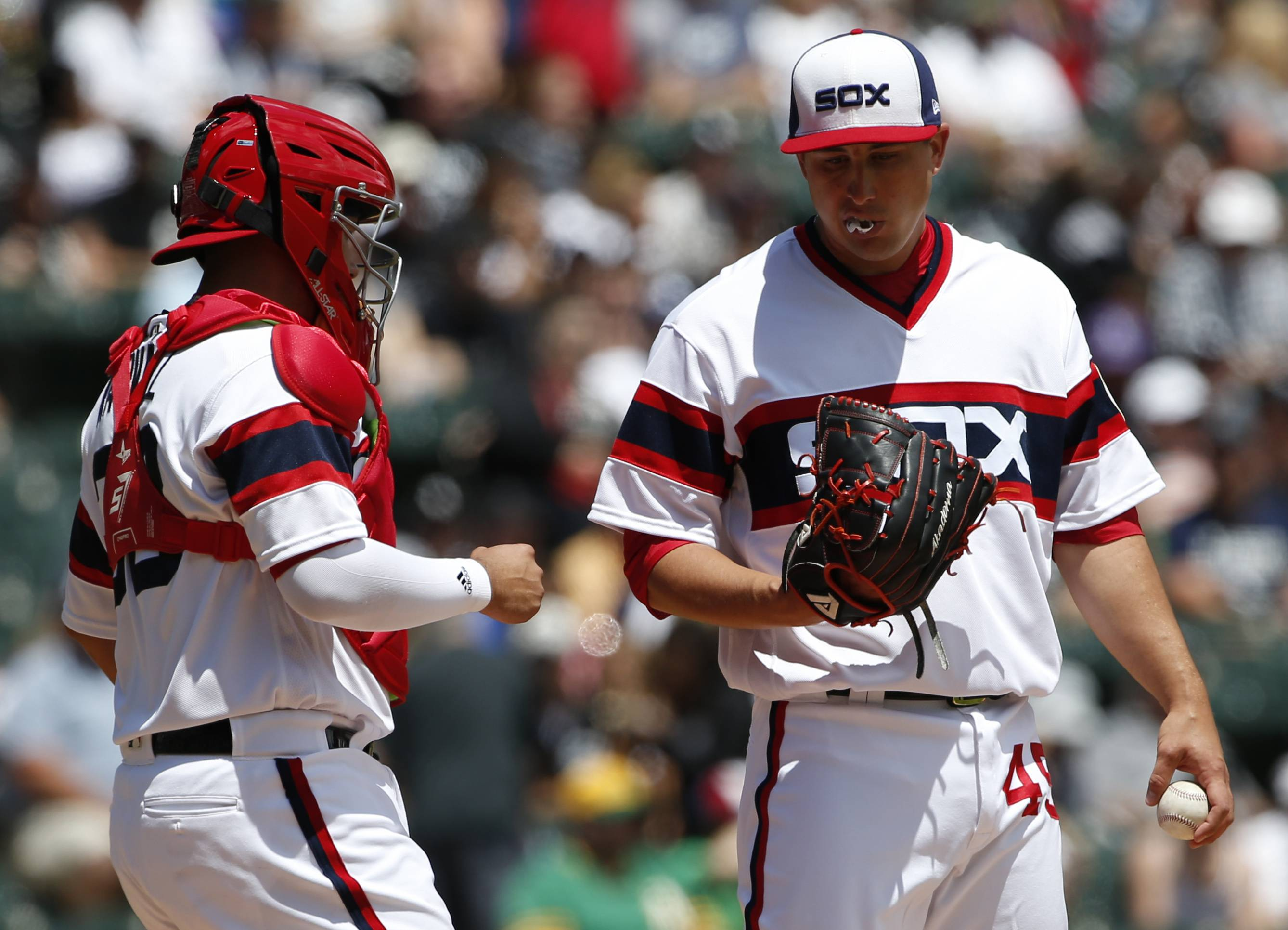 Chicago White Sox starting pitcher Derek Holland, right, listens to catcher Omar Narvaez during the first inning against the Oakland Athletics Sunday in Chicago.