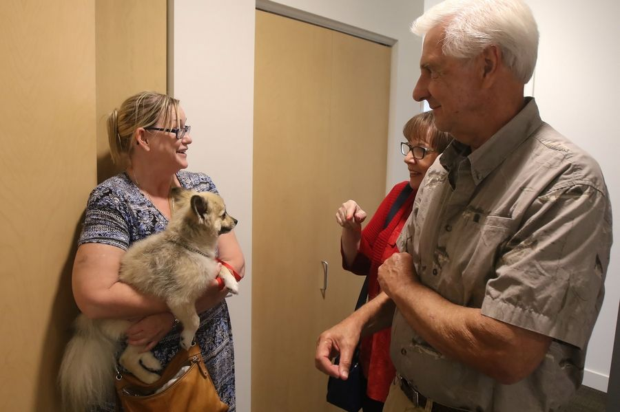 Nancy Logue holds her dog, Norman, as she talks to Donna and Ken Lung of Inverness while they tour her apartment at PhilHaven in Wheeling. The 50-unit housing development provides apartments for people with disabilities and those previously homeless.
