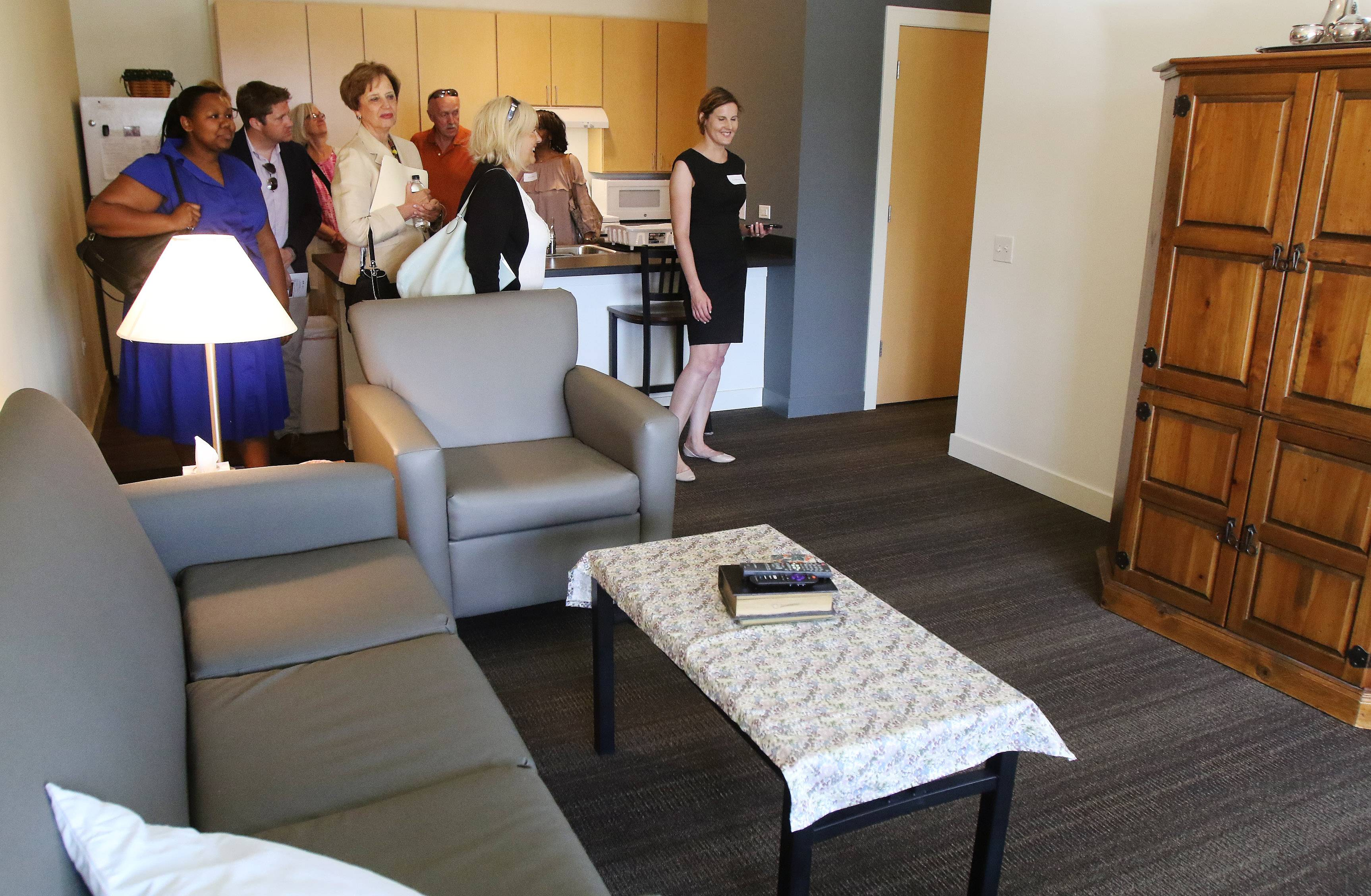 A group tours an apartment during Monday's grand opening of PhilHaven in Wheeling. The 50-unit housing development provides apartments for people with disabilities and those previously homeless.