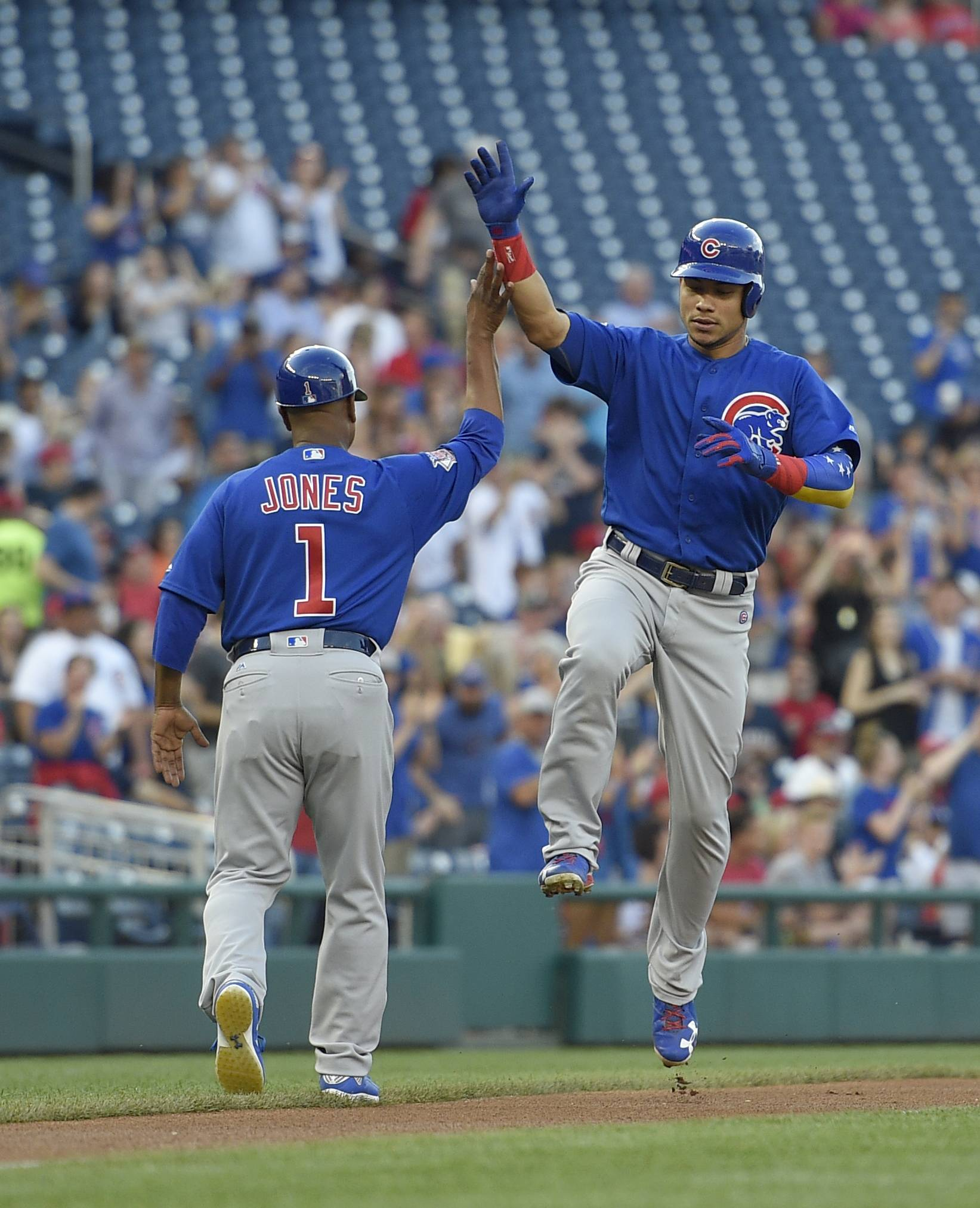 Chicago Cubs' Willson Contreras, right, celebrates his home run with third base coach Gary Jones (1) as he rounds third during the first inning of a baseball game against the Washington Nationals, Monday, June 26, 2017, in Washington. (AP Photo/Nick Wass)