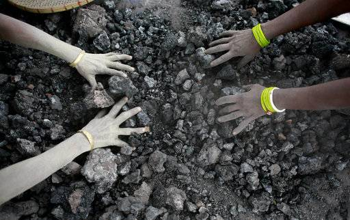 FILE - In this Monday, Dec. 14, 2015, file photo, Indian women use bare hands to pick reusable pieces from heaps of used coal discarded by a carbon factory in Gauhati, India. The world's biggest coal users - China, the United States and India - have boosted coal mining in 2017, in an abrupt departure from last year's record global decline for the heavily polluting fuel and a setback to efforts to rein in climate change emissions. (AP Photo/ Anupam Nath, File)