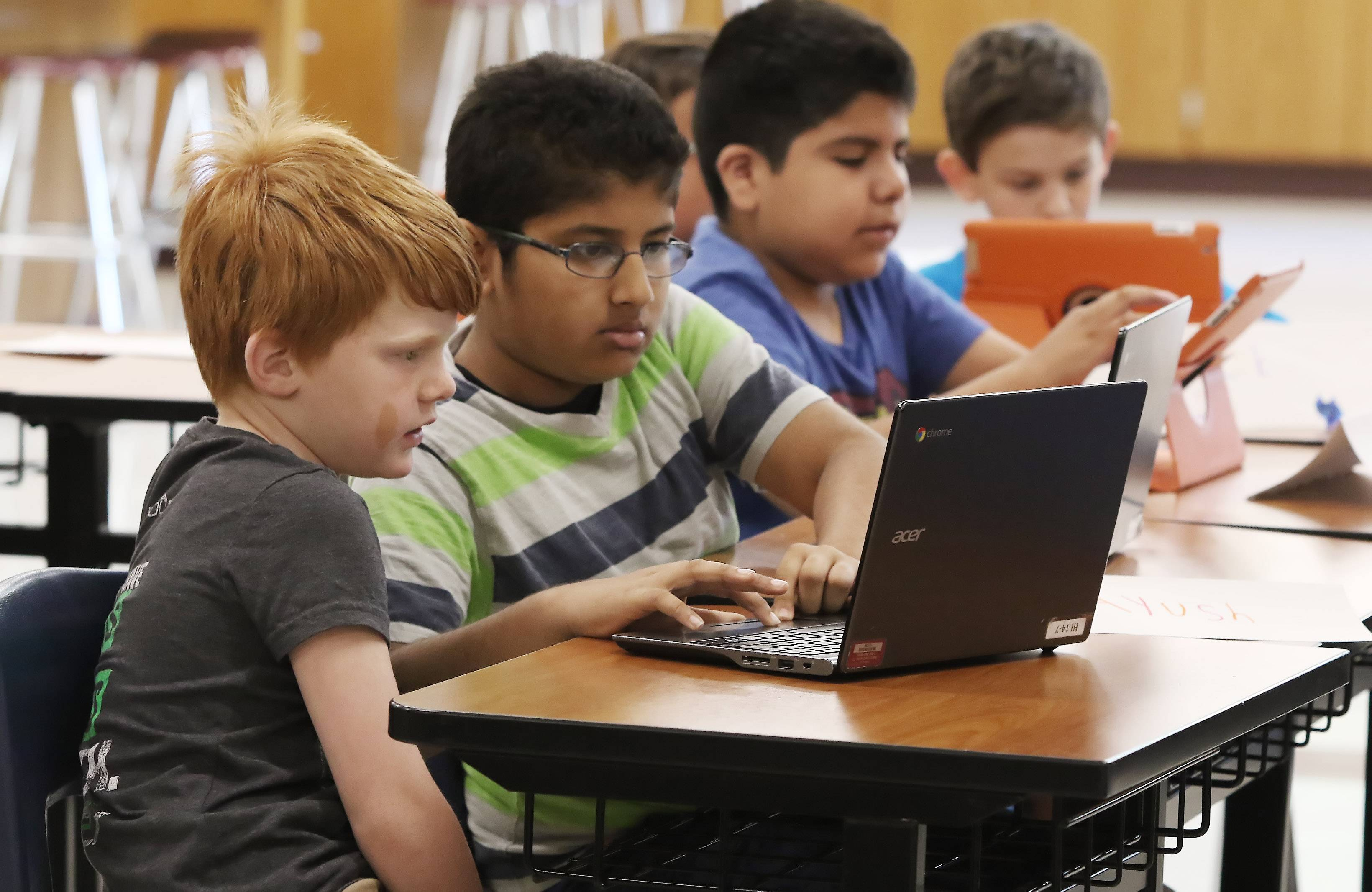 Second grader Jack Boller, left, gets help from fourth grader Ayush Patel as they look at different apps in the Technology at Your Fingertips class Tuesday during Libertyville Elementary District 70 summer school at Highland Middle School.