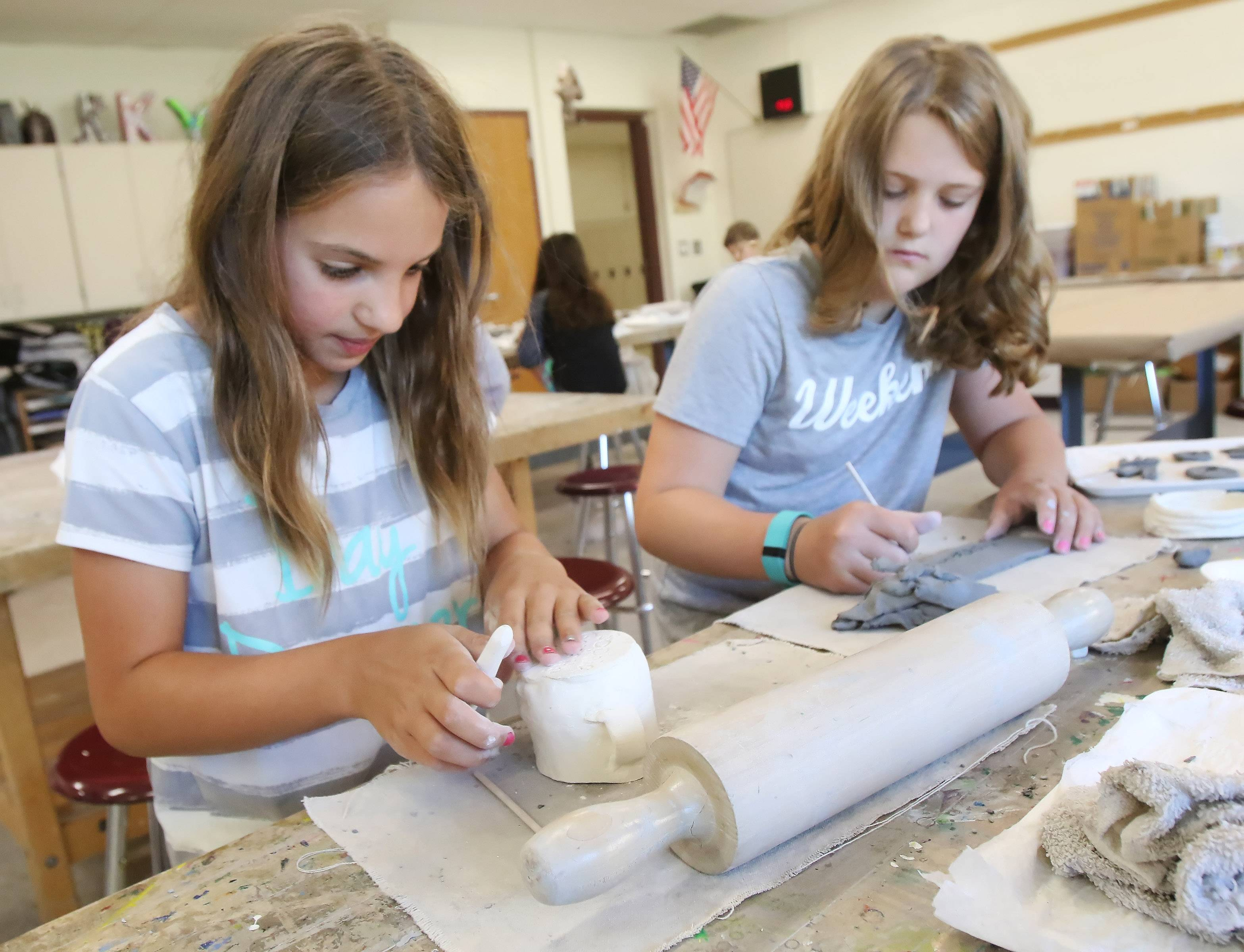 Fifth graders Sophia Griffith, left, and Hannah Babcock work on their clay projects in Intro to Ceramics class Tuesday during Libertyville Elementary District 70 summer school at Highland Middle School.