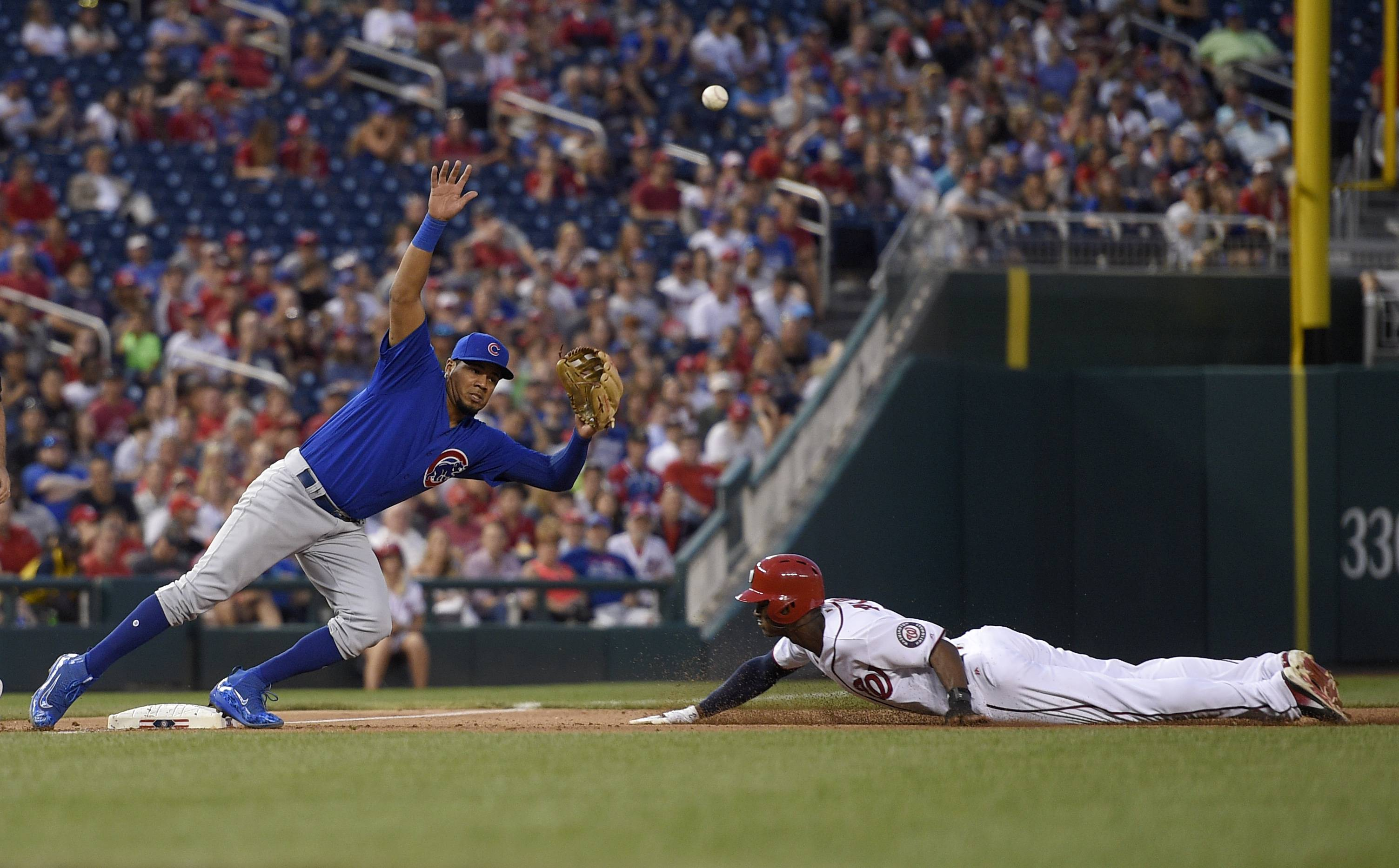 The ball flies past Chicago Cubs third baseman Jeimer Candelario, left, as Washington Nationals' Michael Taylor, right, steals third during the fourth inning of a baseball game, Tuesday, June 27, 2017, in Washington. Taylor went on to score on the play. Chicago Cubs catcher Miguel Montero was charged with a throwing error on the play.(AP Photo/Nick Wass)