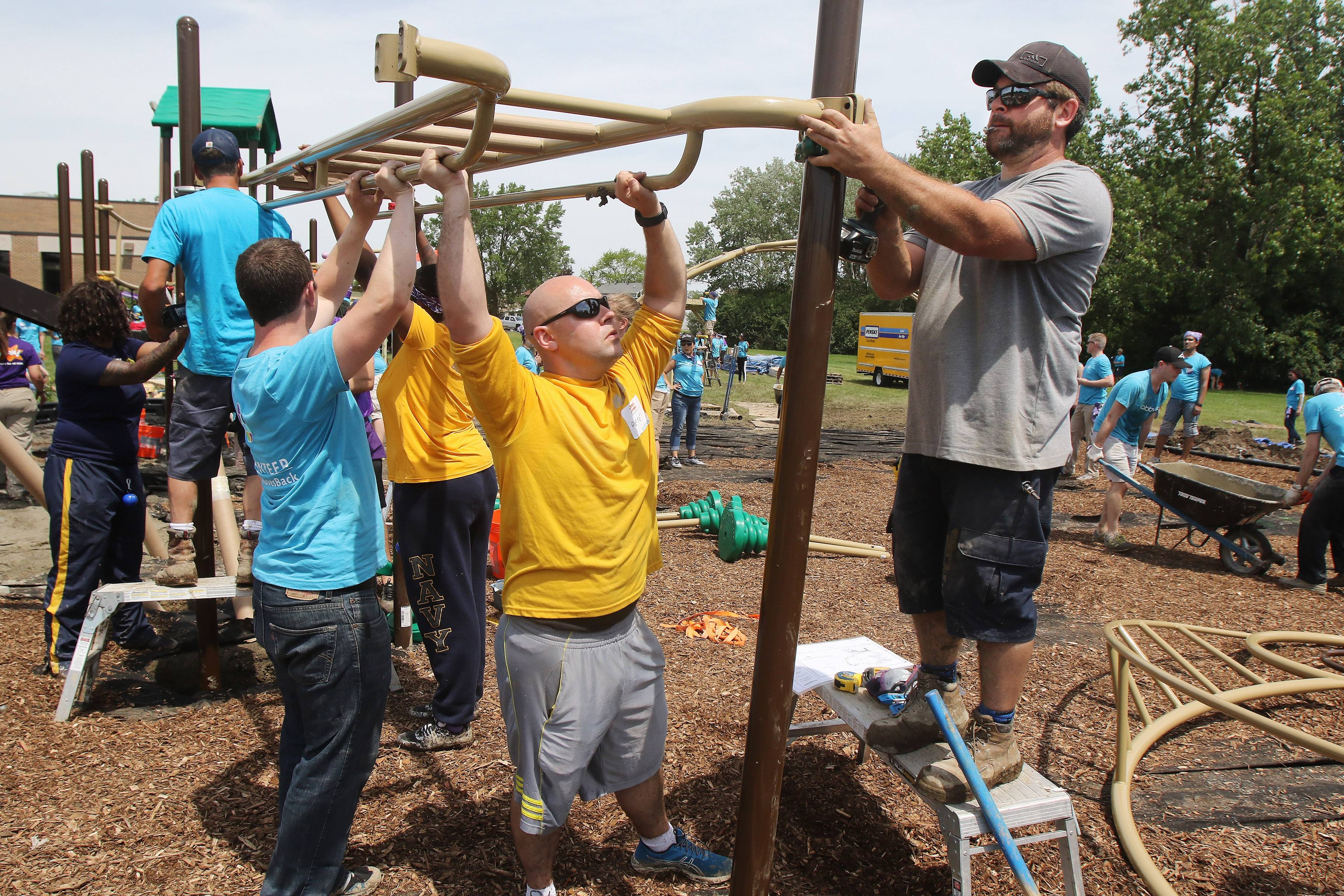 Community volunteer Pat Mazza, right, and Petty Ofc. Pete Peterson join other volunteers to attach monkey bars for a new playground Thursday at A.J. Katzenmaier Academy in North Chicago. Employees from AbbVie, sailors from Naval Station Great Lakes and local community members joined KaBOOM! to work on the project.
