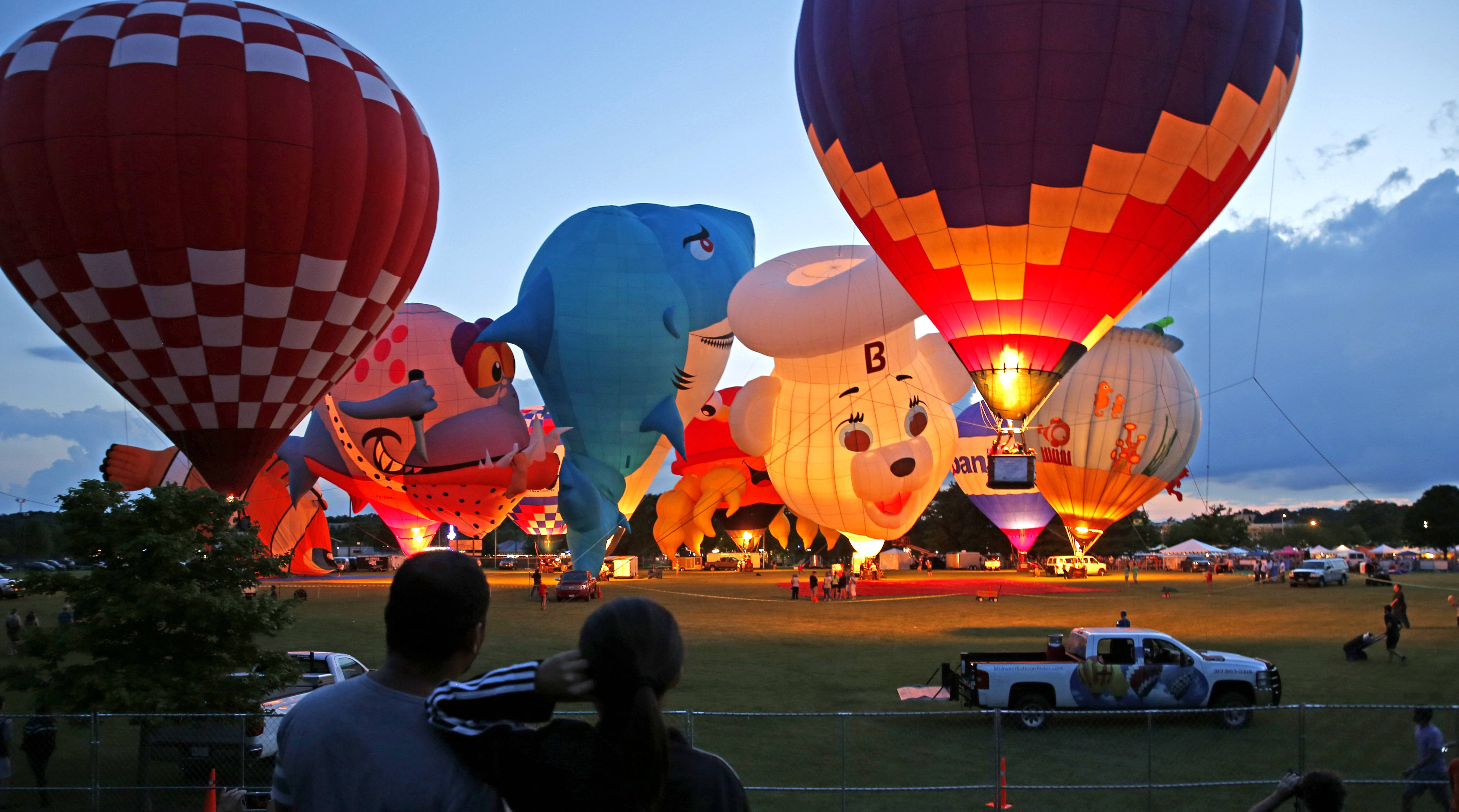 "Tethered balloons light up for a ""balloon glow"" during the opening night of the Eyes to the Skies Festival in Lisle."