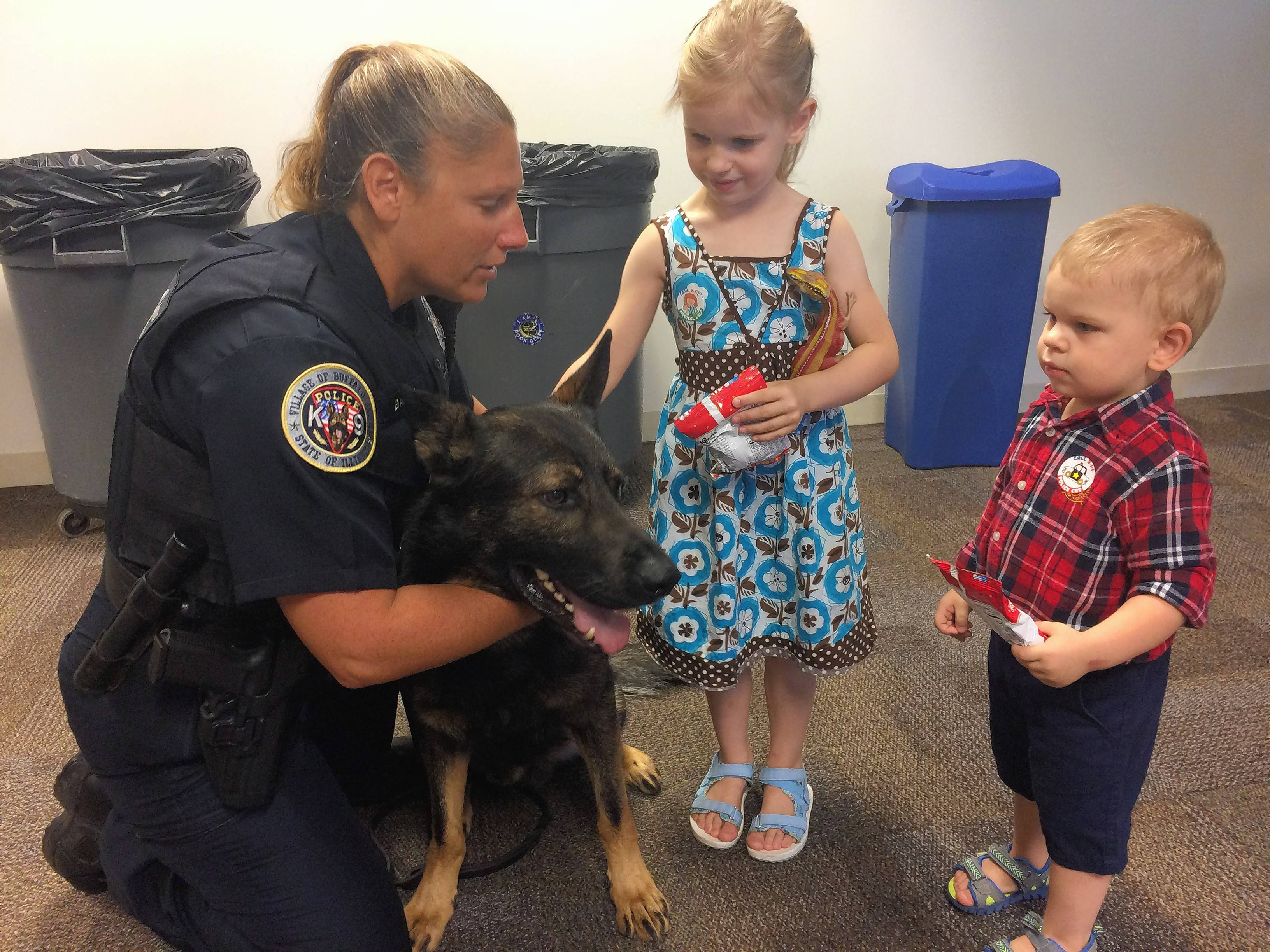 Zofia Mroczkowski, 5, and her brother Arsen, 2, greet Buffalo Grove police officer Danielle Baron and Hogyn the German shepherd at the Vernon Area Public Library in Lincolnshire on Friday.