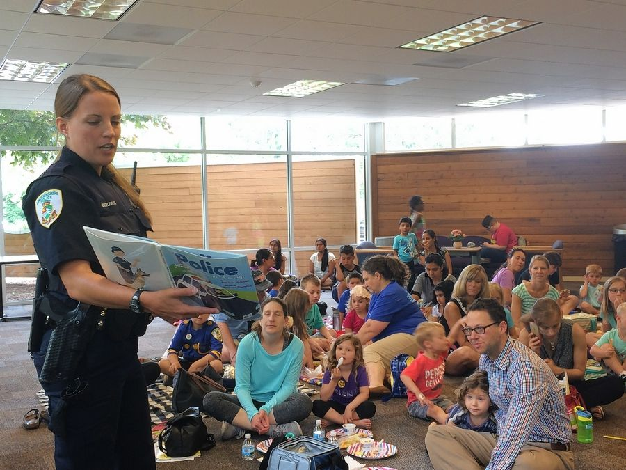 Lincolnshire police officer Bethany Brown reads to families Friday during the Vernon Area Public Library's Picnic With Police event.