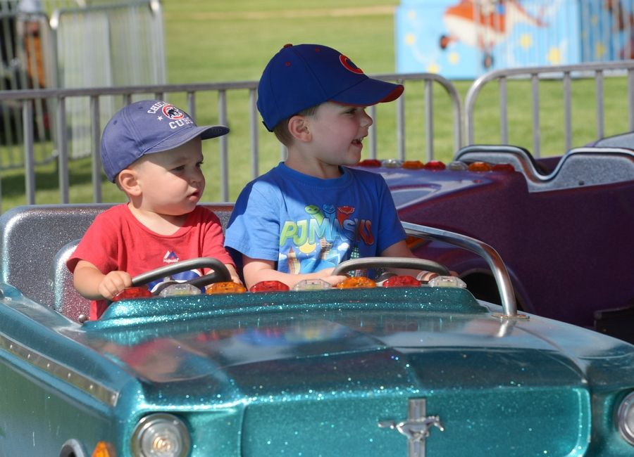 Chase Michel, 2, of Grayslake, and his brother Luke, 4, ride in a car together during the Grayslake Family Picnic Saturday at Central Park.