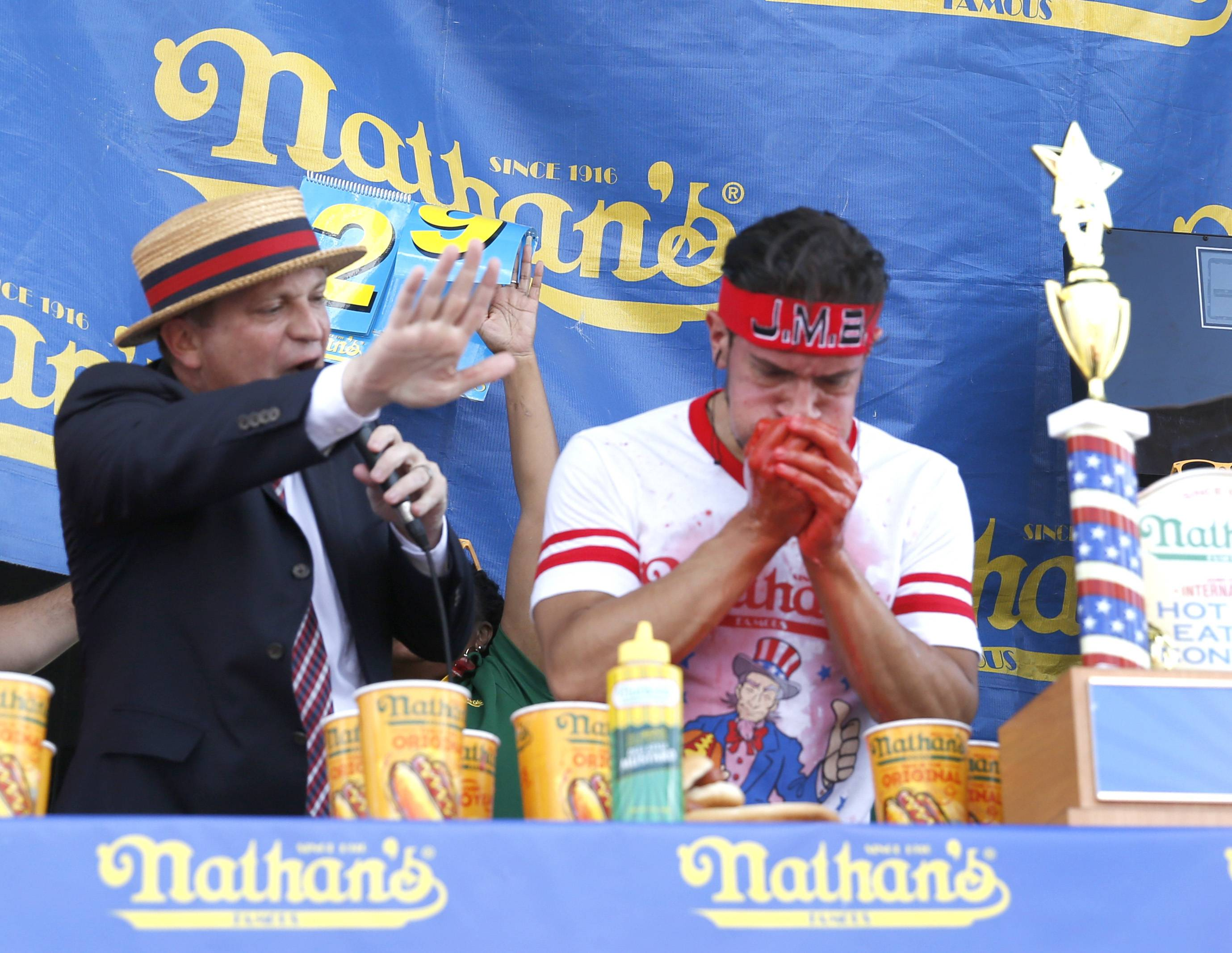 Juan Rodriguez, right, of Crestwood, wins a hot dog-eating contest Saturday at Naperville's Ribfest by downing 30½ dogs in 10 minutes as Emcee Sam Barclay provides the encouragement. Rodriguez qualified for a spot in Nathan's Famous Fourth of July Hot Dog Eating Contest in Coney Island, New York.